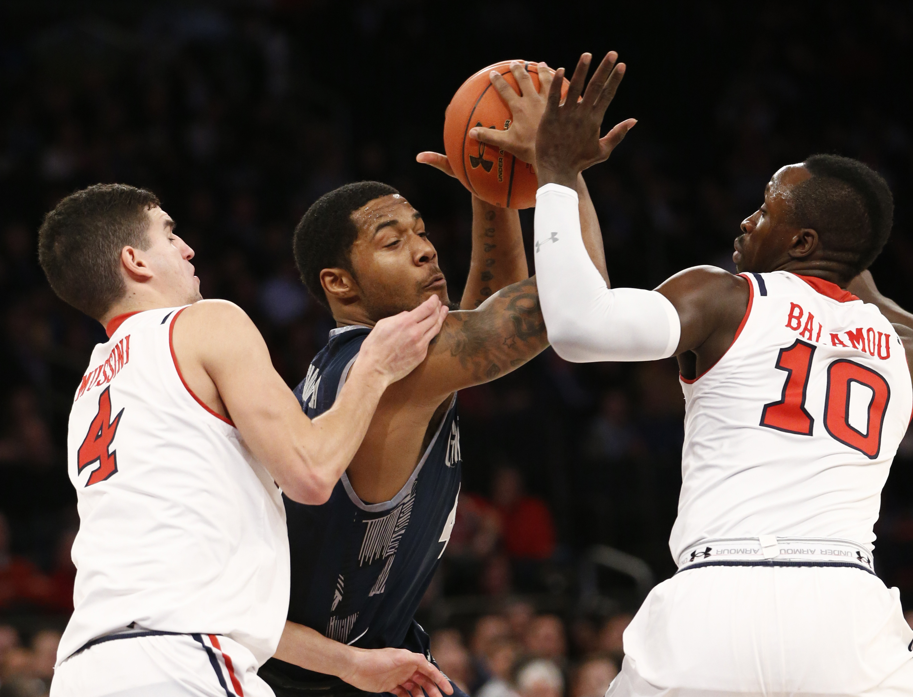 St. John's guard Federico Mussini (4) and Felix Balamou (10) defend Georgetown guard D'Vauntes Smith-Rivera in the first half of an NCAA college basketball game at Madison Square Garden in New York, Wednesday, Jan. 13, 2016. (AP Photo/Kathy Willens)