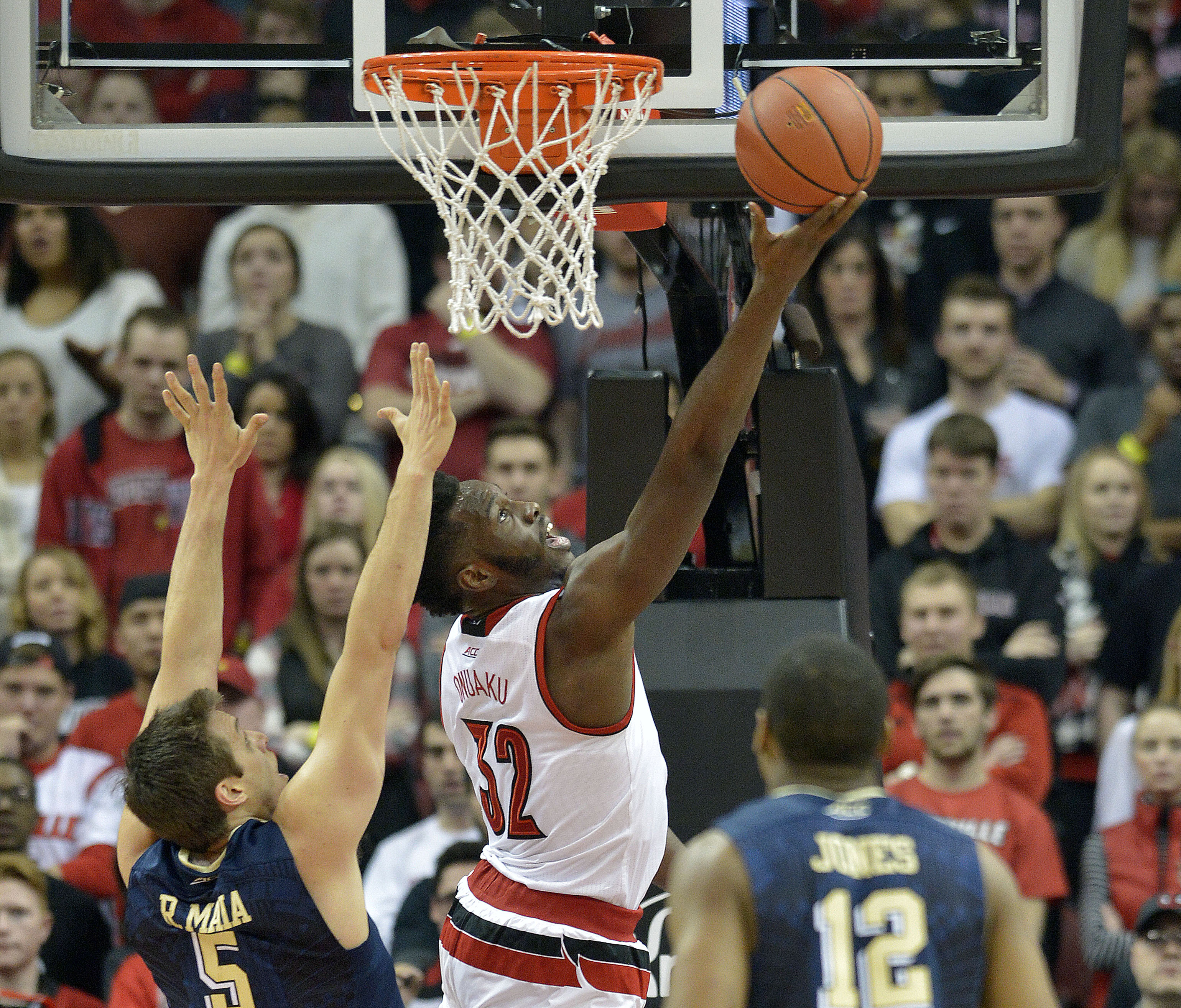 Louisville's Chinanu Onuaku (32) attempts a layup past the defense of Pittsburgh's Rafael Maia (5) and Chris Jones (12) during the first half of an NCAA college basketball game, Thursday, Jan. 14, 2016, in Louisville, Ky. (AP Photo/Timothy D. Easley)