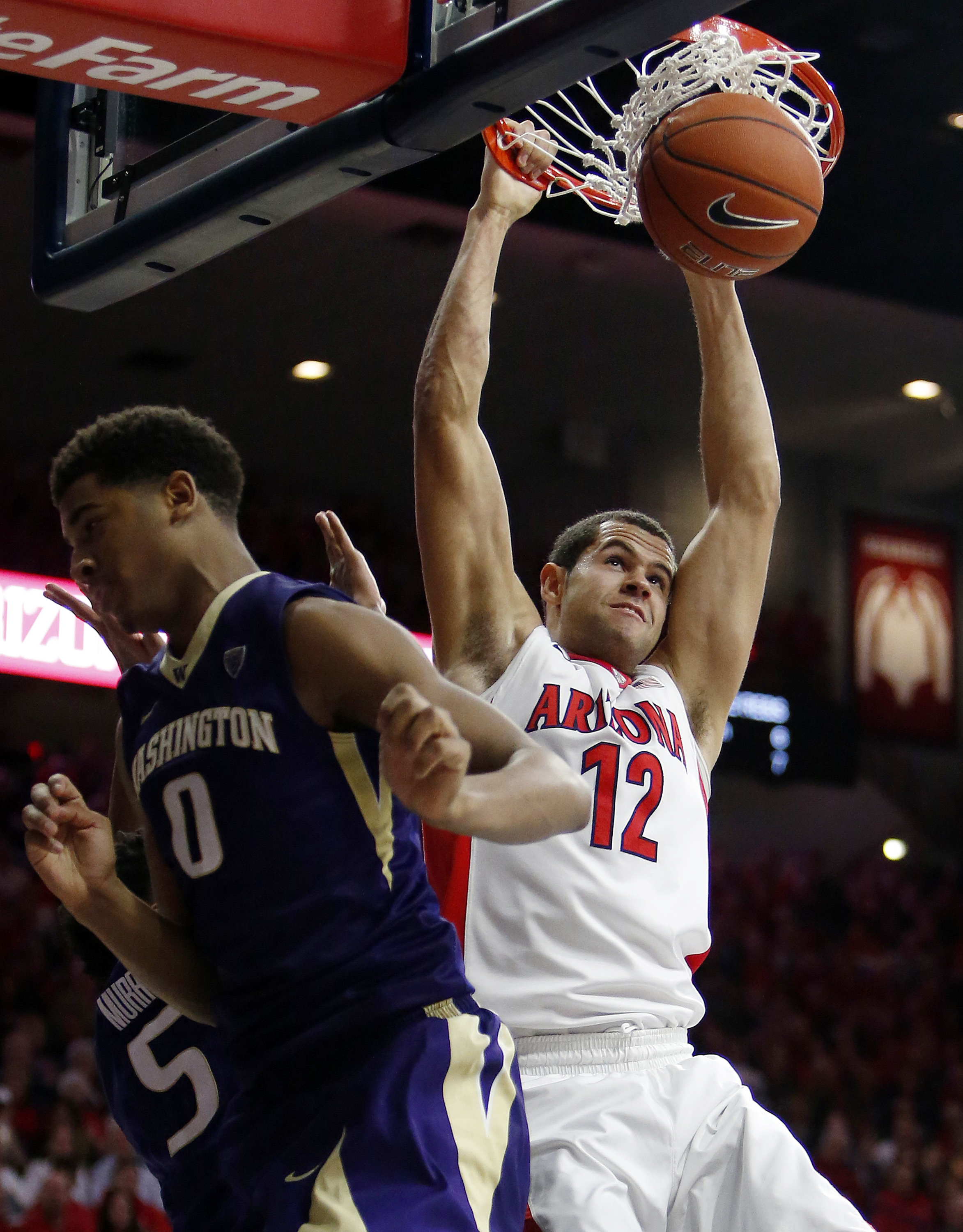 Arizona forward Ryan Anderson (12) dunks next to Washington guard Dejounte Murray (5) and forward Marquese Chriss (0) during the second half of an NCAA college basketball game Thursday, Jan. 14, 2016, in Tucson, Ariz. Arizona defeated Washington 99-67. (A