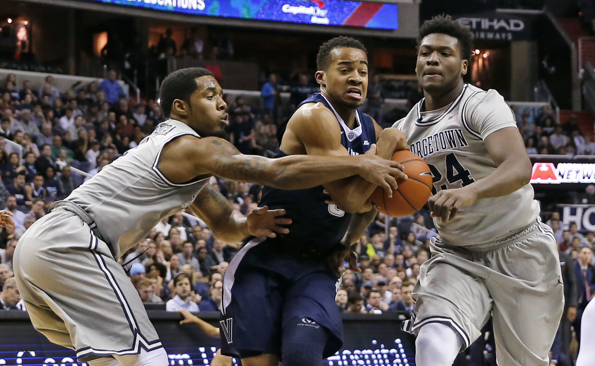 Villanova guard Phil Booth (5) tries to get past Georgetown guard D'Vauntes Smith-Rivera, left, and forward Marcus Derrickson during the first half of an NCAA college basketball game, Saturday, Jan. 16, 2016, in Washington. (AP Photo/Alex Brandon)