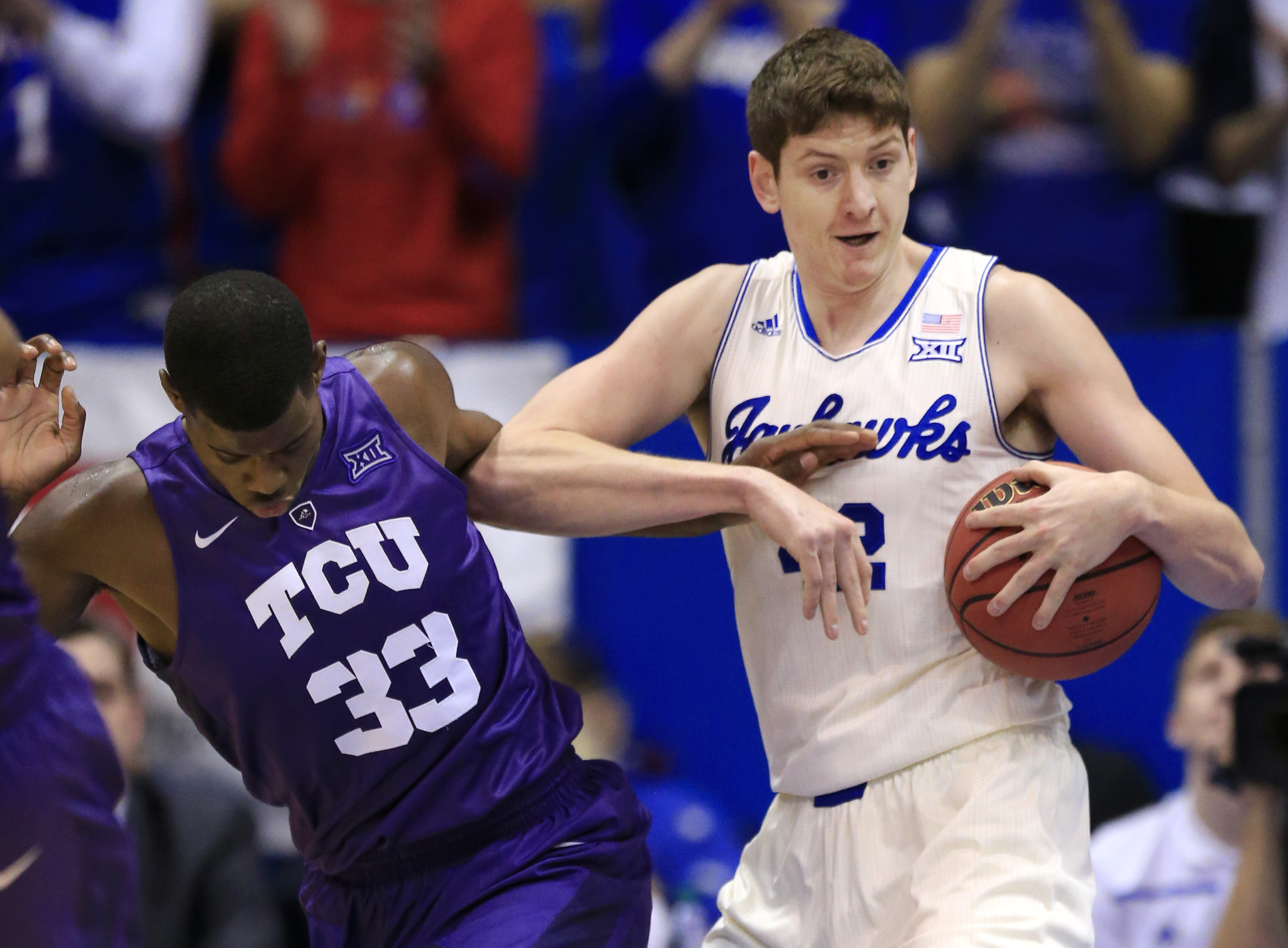 Kansas forward Hunter Mickelson (42) rebounds against TCU forward Chris Washburn (33) during the first half of an NCAA college basketball game in Lawrence, Kan., Saturday, Jan. 16, 2016. (AP Photo/Orlin Wagner)