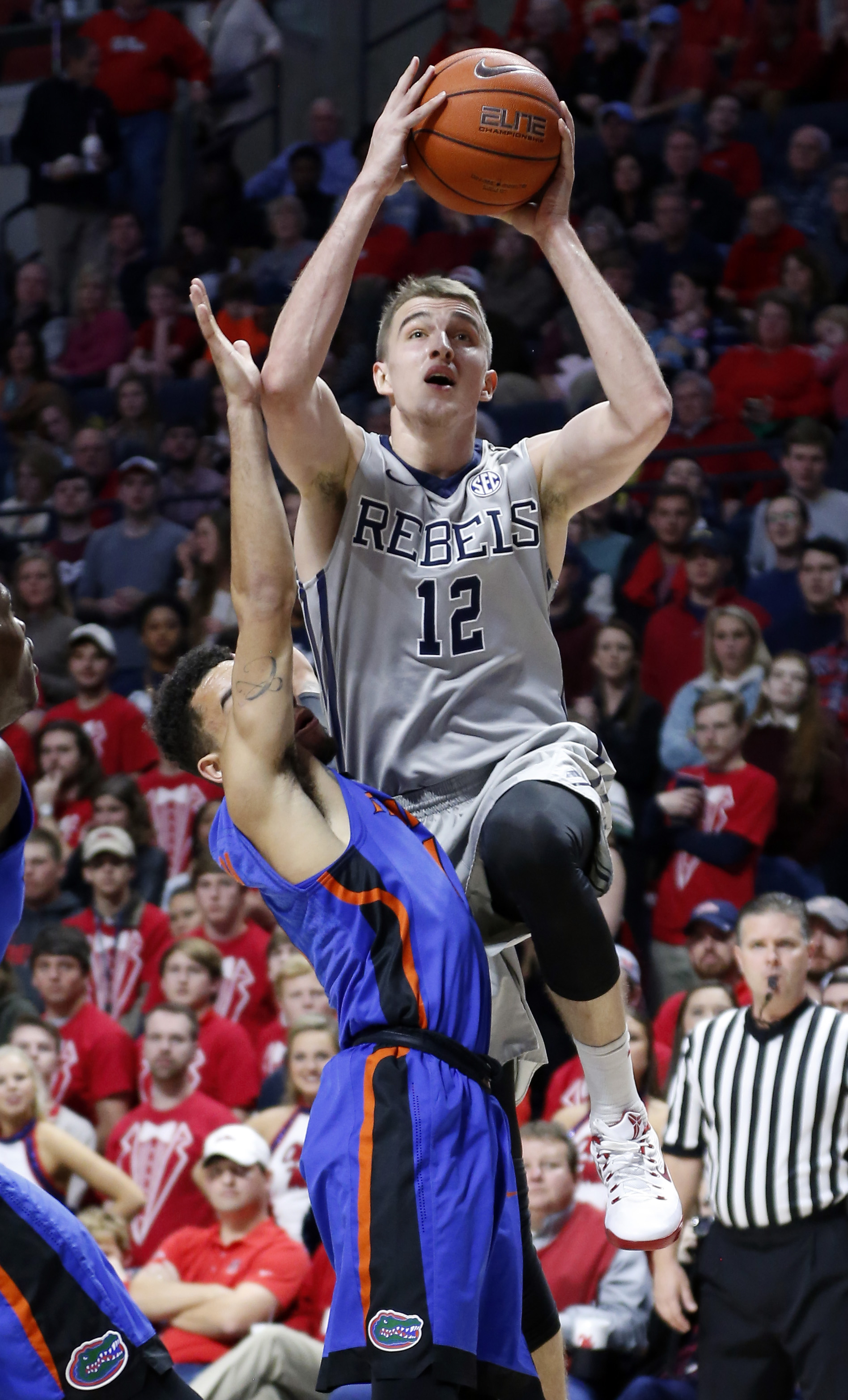 Mississippi forward Tomasz Gielo (12) attempts a shot over Florida guard Chris Chiozza (11) in the first half of an NCAA college basketball game in Oxford, Miss., Saturday, Jan. 16, 2016. (AP Photo/Rogelio V. Solis)