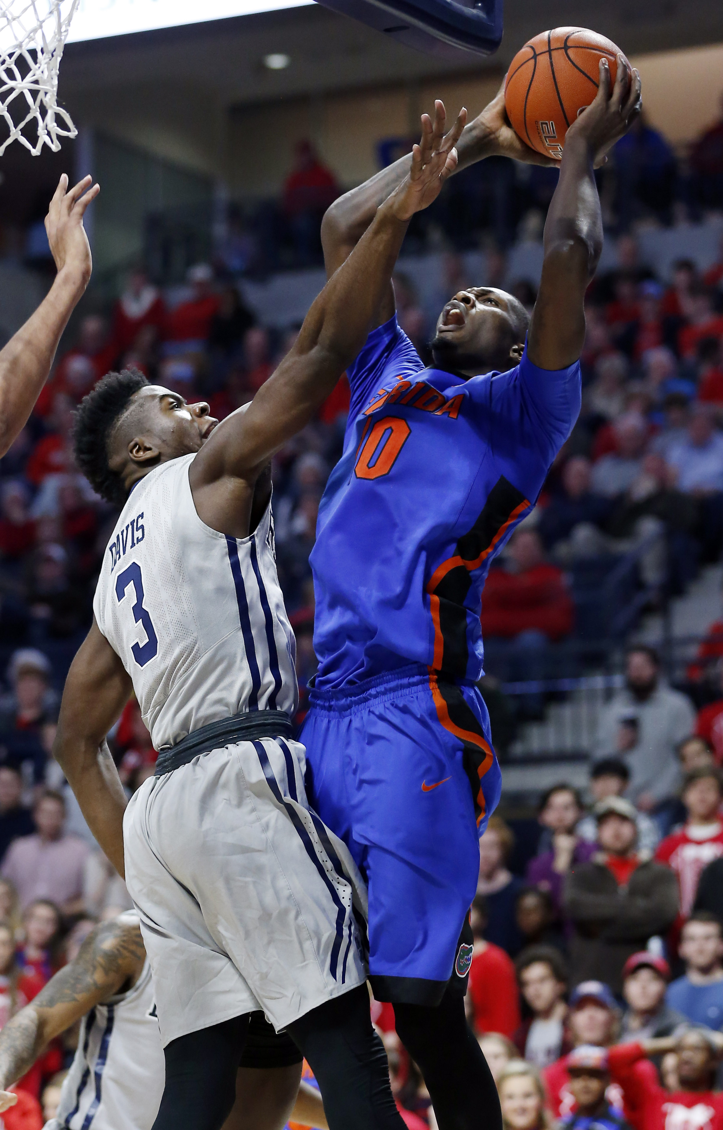 Florida forward Dorian Finney-Smith (10) attempts a shot at the basket past the defense of Mississippi guard Terence Davis (3) in the second half of an NCAA college basketball game in Oxford, Miss., Saturday, Jan. 16, 2016. Florida won 80-71. (AP Photo/Ro