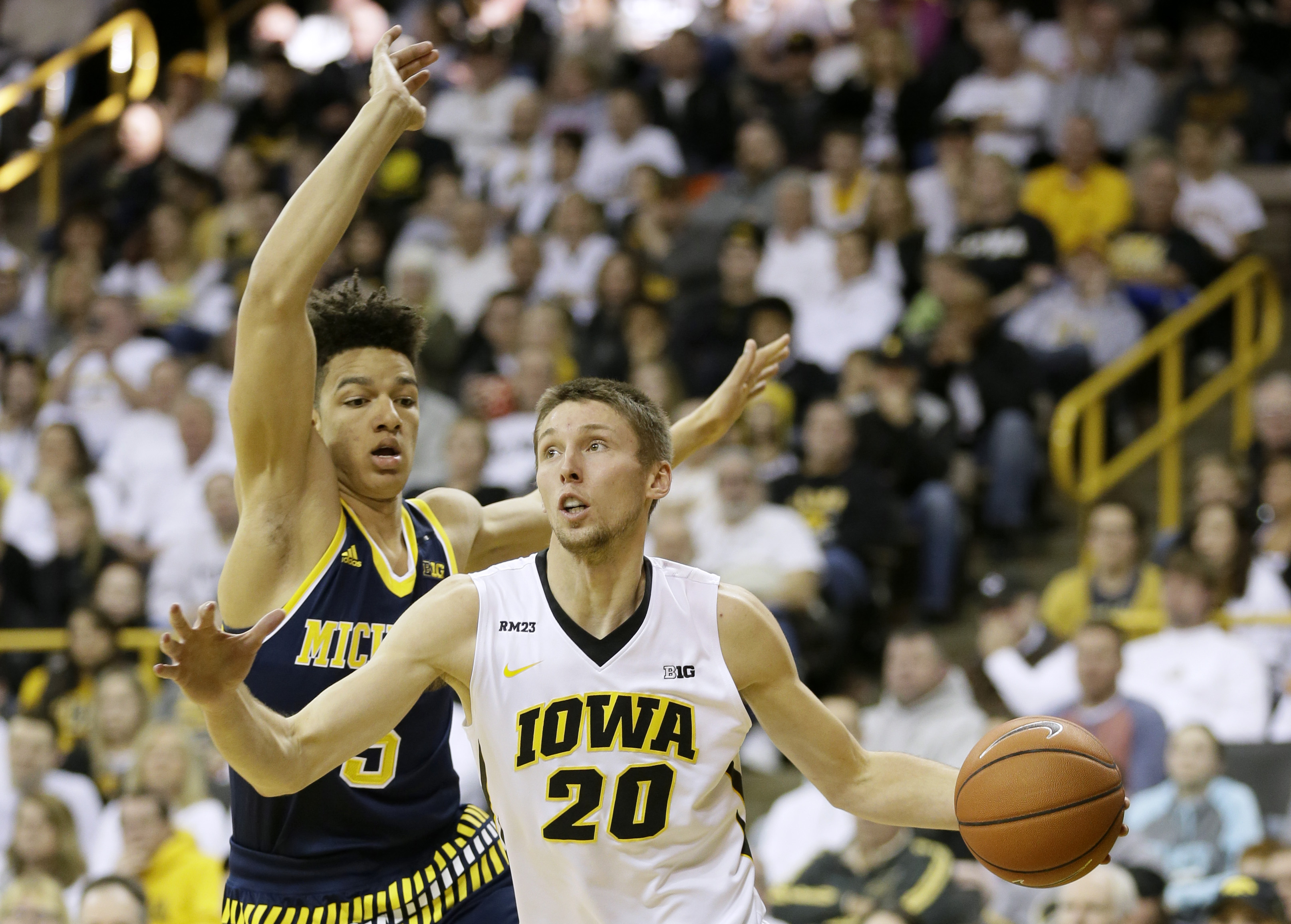 Iowa forward Jarrod Uthoff drives past Michigan forward D.J. Wilson, left, during the first half of an NCAA college basketball game, Sunday, Jan. 17, 2016, in Iowa City, Iowa. (AP Photo/Charlie Neibergall)