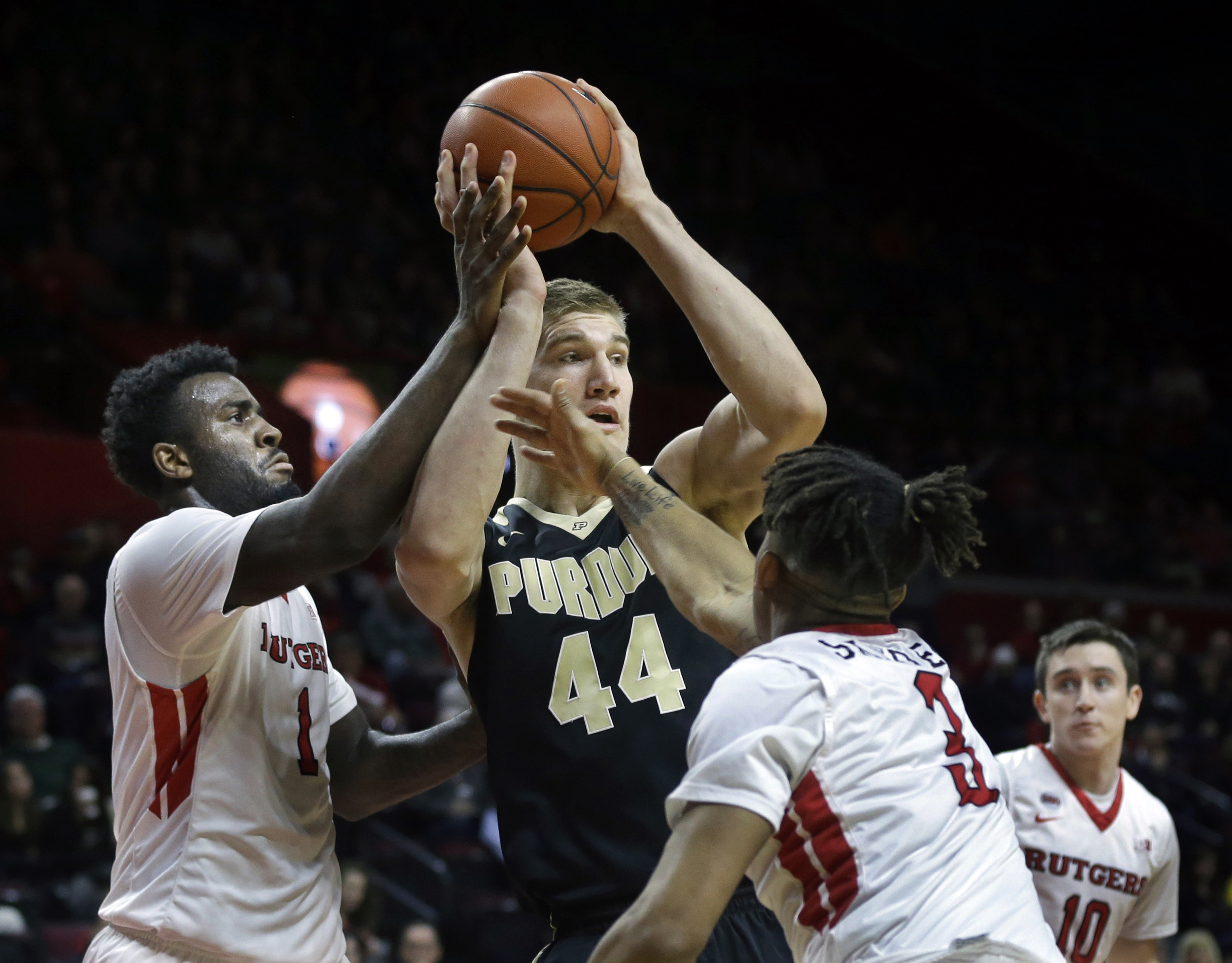 Purdue center Isaac Haas (44) looks to make a pass as he is defended by Rutgers forward D.J. Foreman (1) an guard Corey Sanders (3) during the first half of an NCAA college basketball game, Monday, Jan. 18, 2016, in Piscataway, N.J. (AP Photo/Mel Evans)