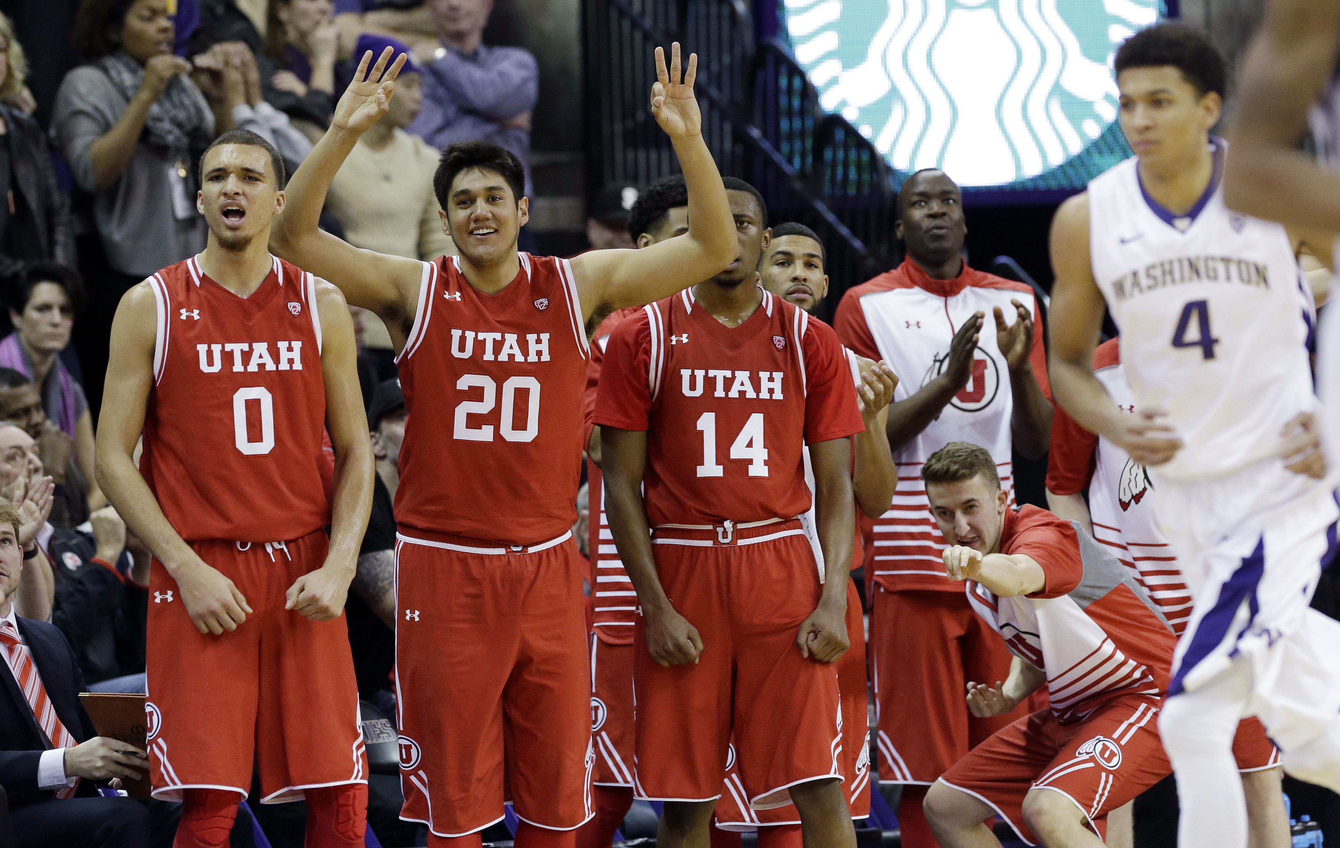 Players on Utah's bench cheer a 3-point shot late in the second half of an NCAA college basketball game against Washington, Sunday, Jan. 24, 2016, in Seattle. Utah won in overtime, 80-75. (AP Photo/Elaine Thompson)