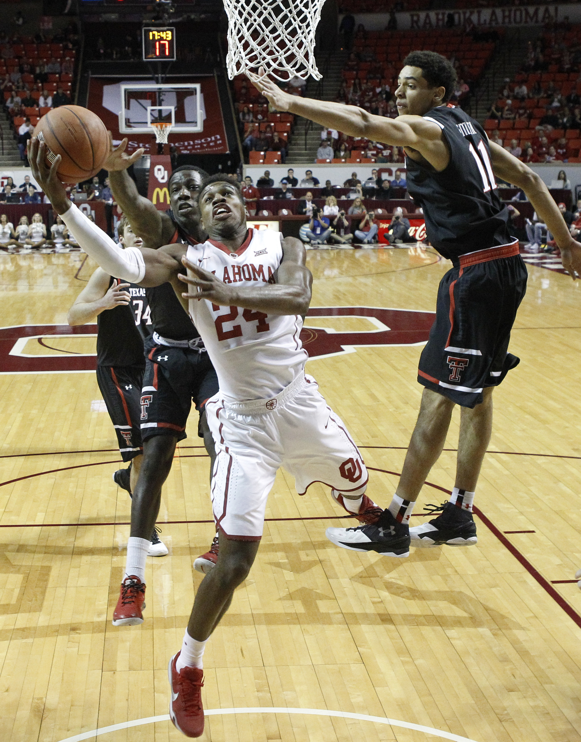 Oklahoma guard Buddy Hield shoots between Texas Tech guard Devaugntah Williams, left, and forward Zach Smith during the first half of an NCAA college basketball game in Norman, Okla., Tuesday, Jan. 26, 2016. (AP Photo/Sue Ogrocki)