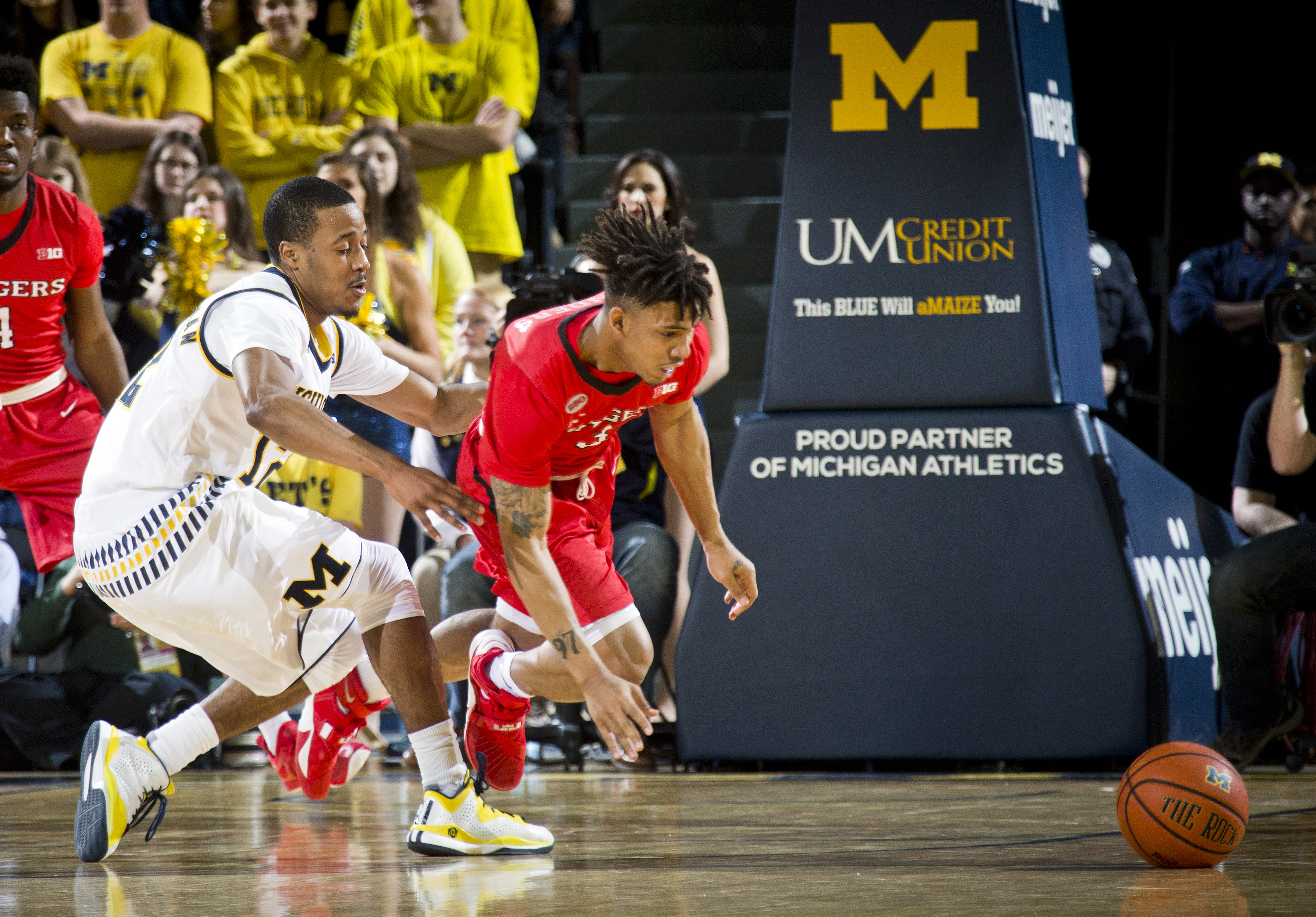 Michigan guard Muhammad-Ali Abdur-Rahkman, left, and Rutgers guard Corey Sanders contest for a loose ball in the first half of an NCAA college basketball game at Crisler Center in Ann Arbor, Mich., Wednesday, Jan. 27, 2016. (AP Photo/Tony Ding)