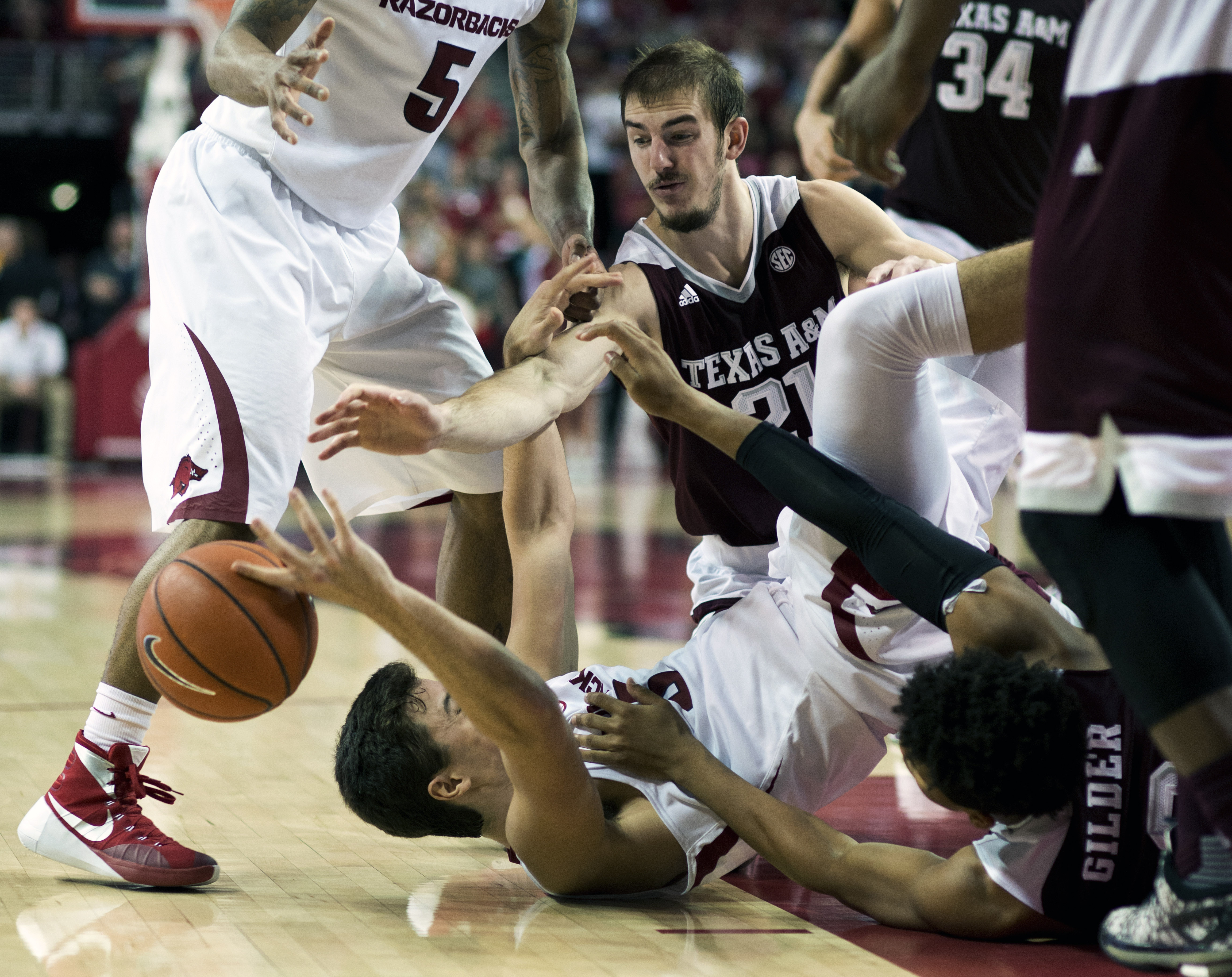 Arkansas' Dusty Hannahs (3) fights for control of the ball against Texas A&M's Alex Caruso (21) in the second half of an NCAA college basketball game in Fayetteville, Ark., Wednesday, Jan. 27, 2016. Arkansas won 74-71. (AP Photo/Sarah Bentham)