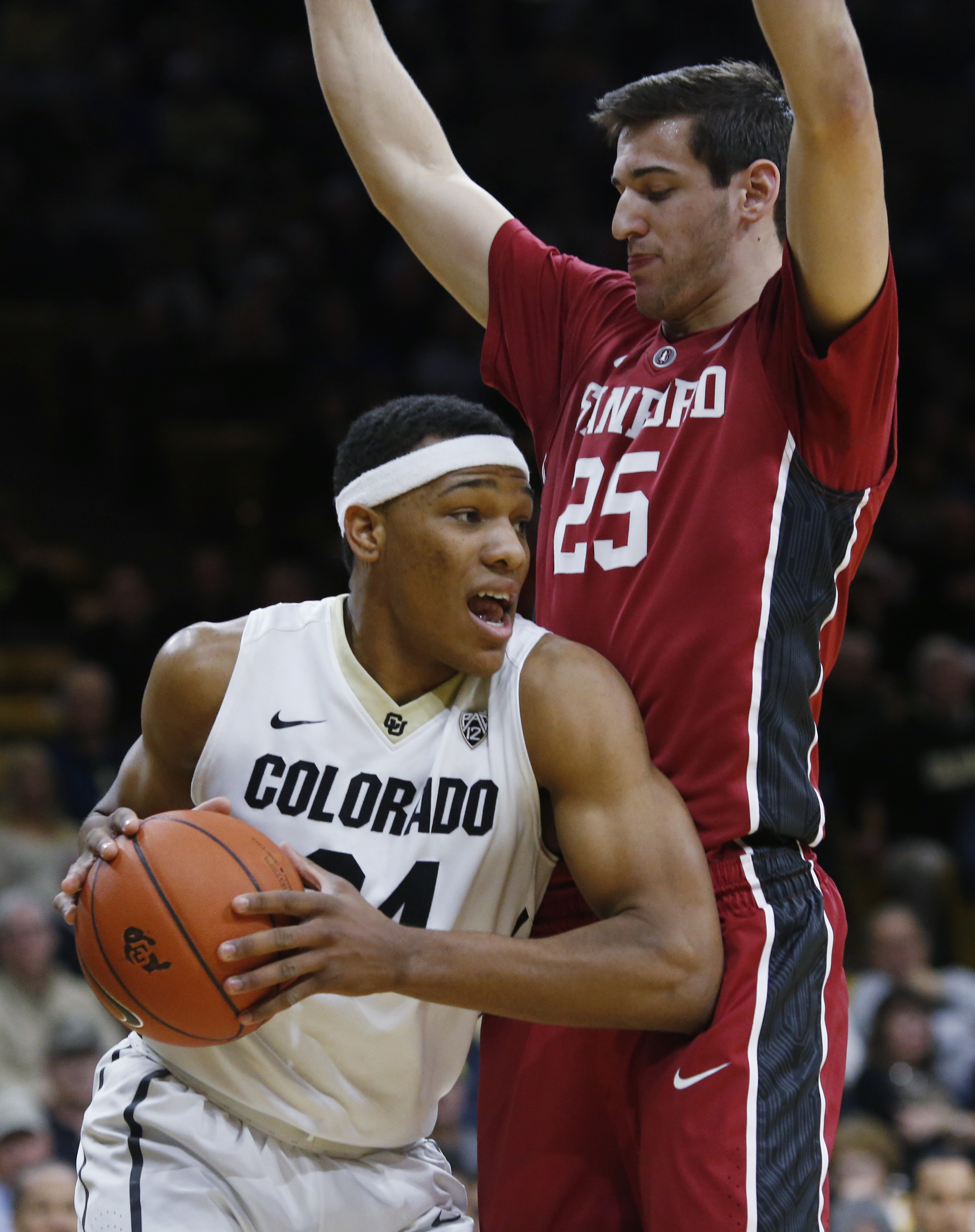 Colorado guard George King, left, looks to pass the ball after pulling in a rebound in front of Stanford forward Rosco Allen during the first half of an NCAA college basketball game Wednesday, Jan. 27, 2016, in Boulder, Colo. (AP Photo/David Zalubowski)