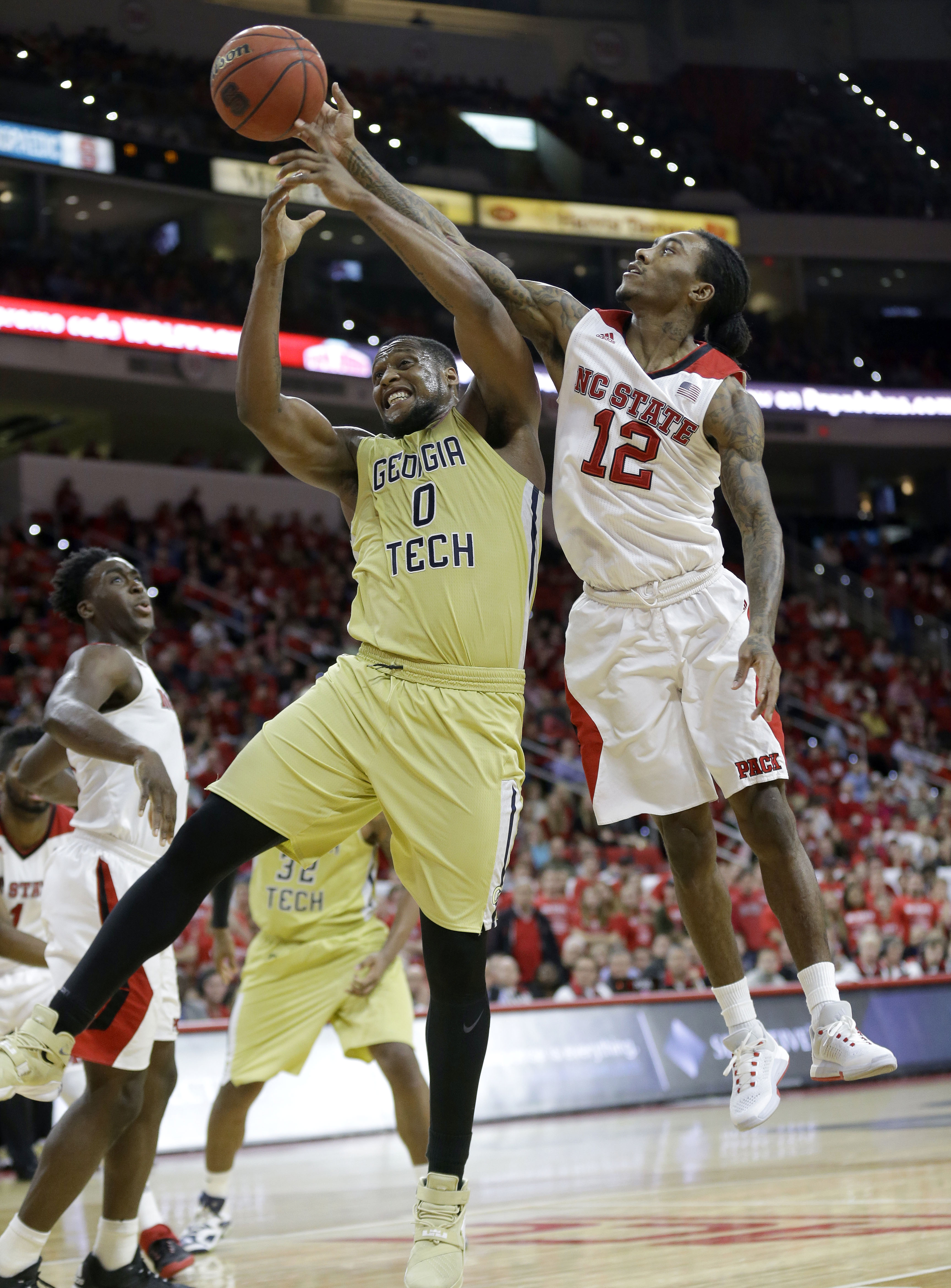 Georgia Tech's Charles Mitchell (0) drives to the basket as North Carolina State's Anthony Barber (12) defends during the second half of an NCAA college basketball game in Raleigh, N.C., Wednesday, Jan. 27, 2016. Georgia Tech won 90-83. (AP Photo/Gerry Br