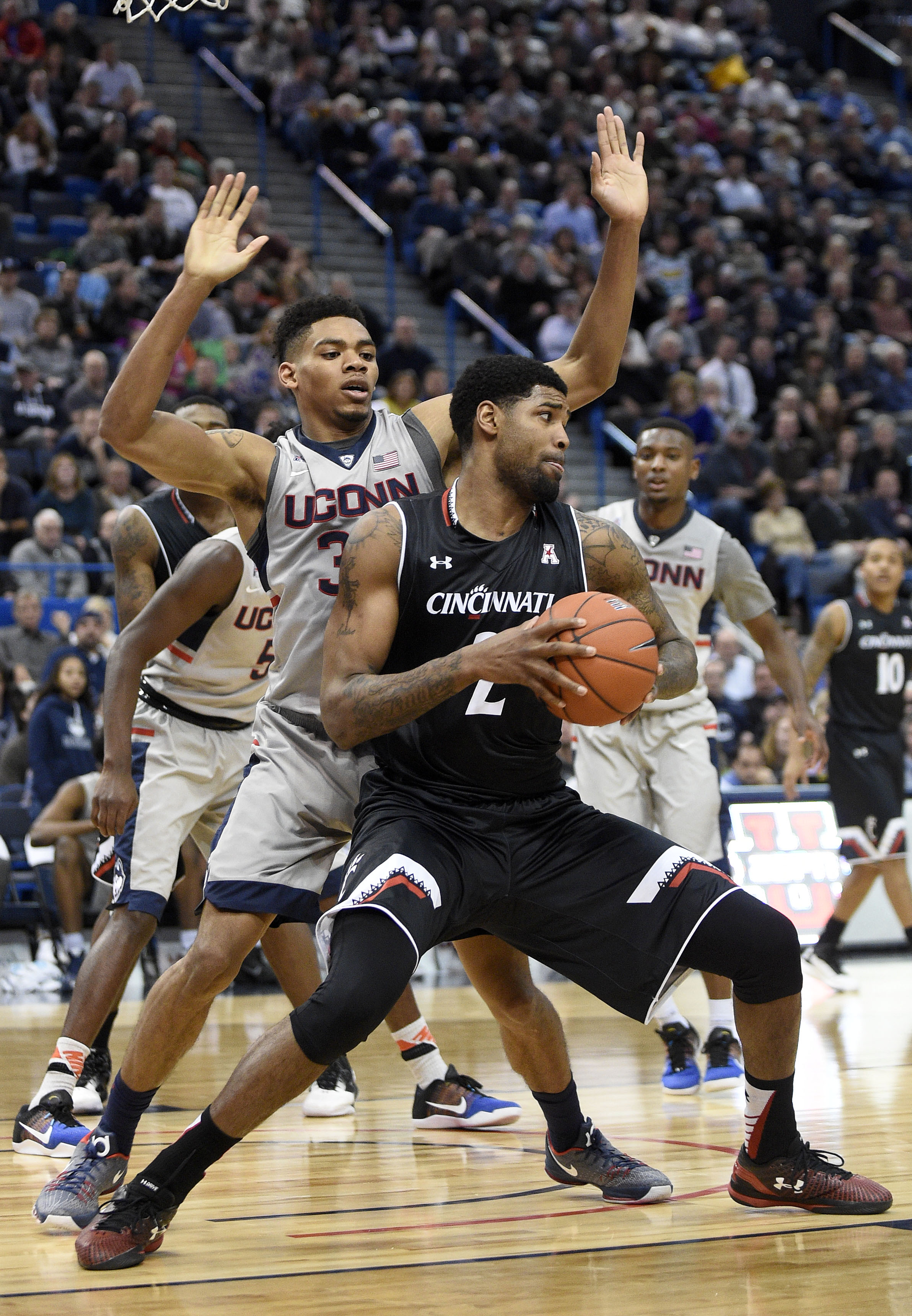 Cincinnati's Octavius Ellis, front, is guarded by Connecticut's Shonn Miller (32) during the first half of an NCAA college basketball game in Hartford, Conn., on Thursday, Jan. 28, 2016. (AP Photo/Fred Beckham)