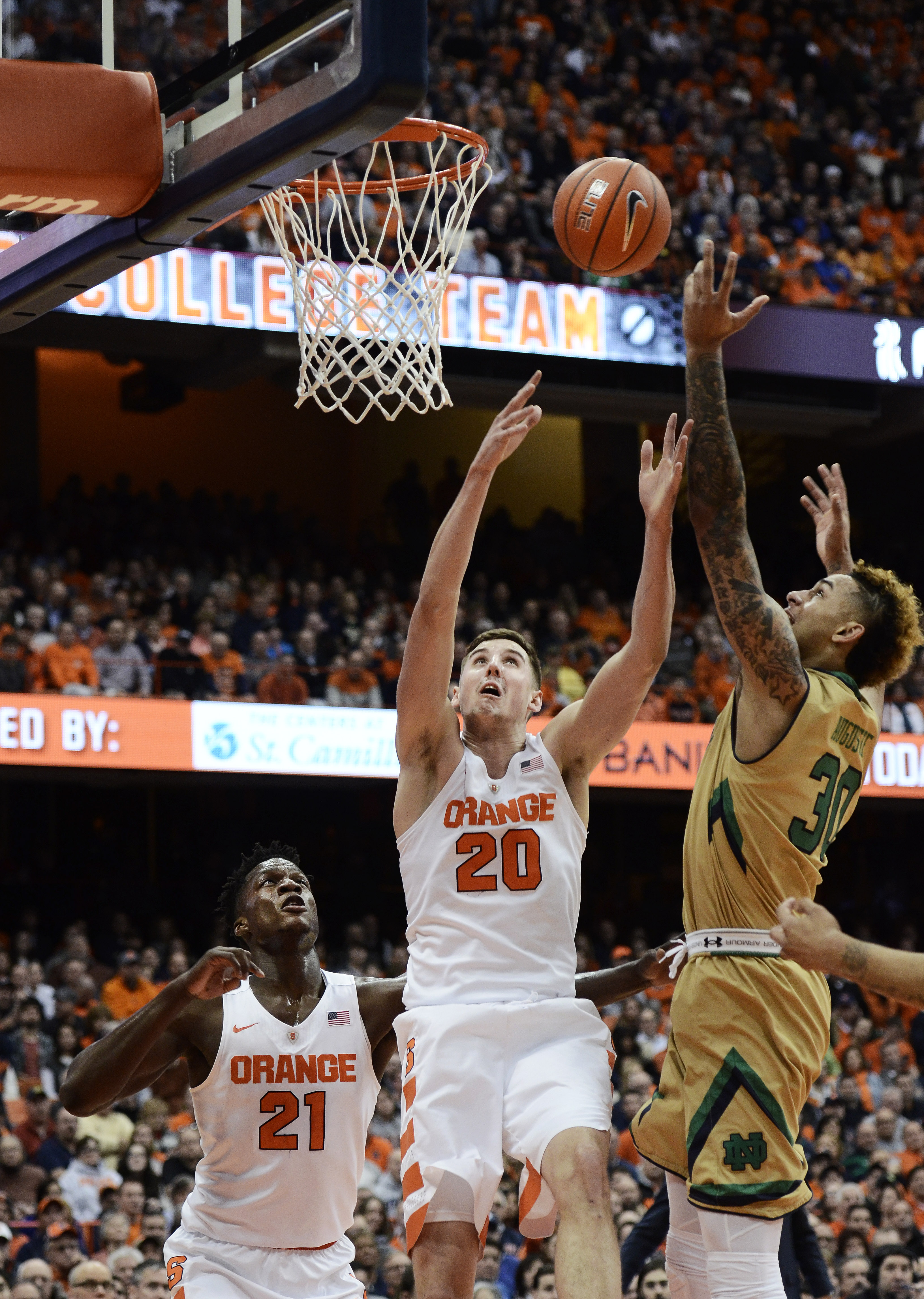 Syracuse's Tyler Lydon, center, attempts to block Notre Dame's Zach Auguste's, right, attempt at a layup during the first half of an NCAA college basketball game at at the Carrier Dome in Syracuse, N.Y., Thursday, Jan. 28, 2016. (AP Photo/Heather Ainswort