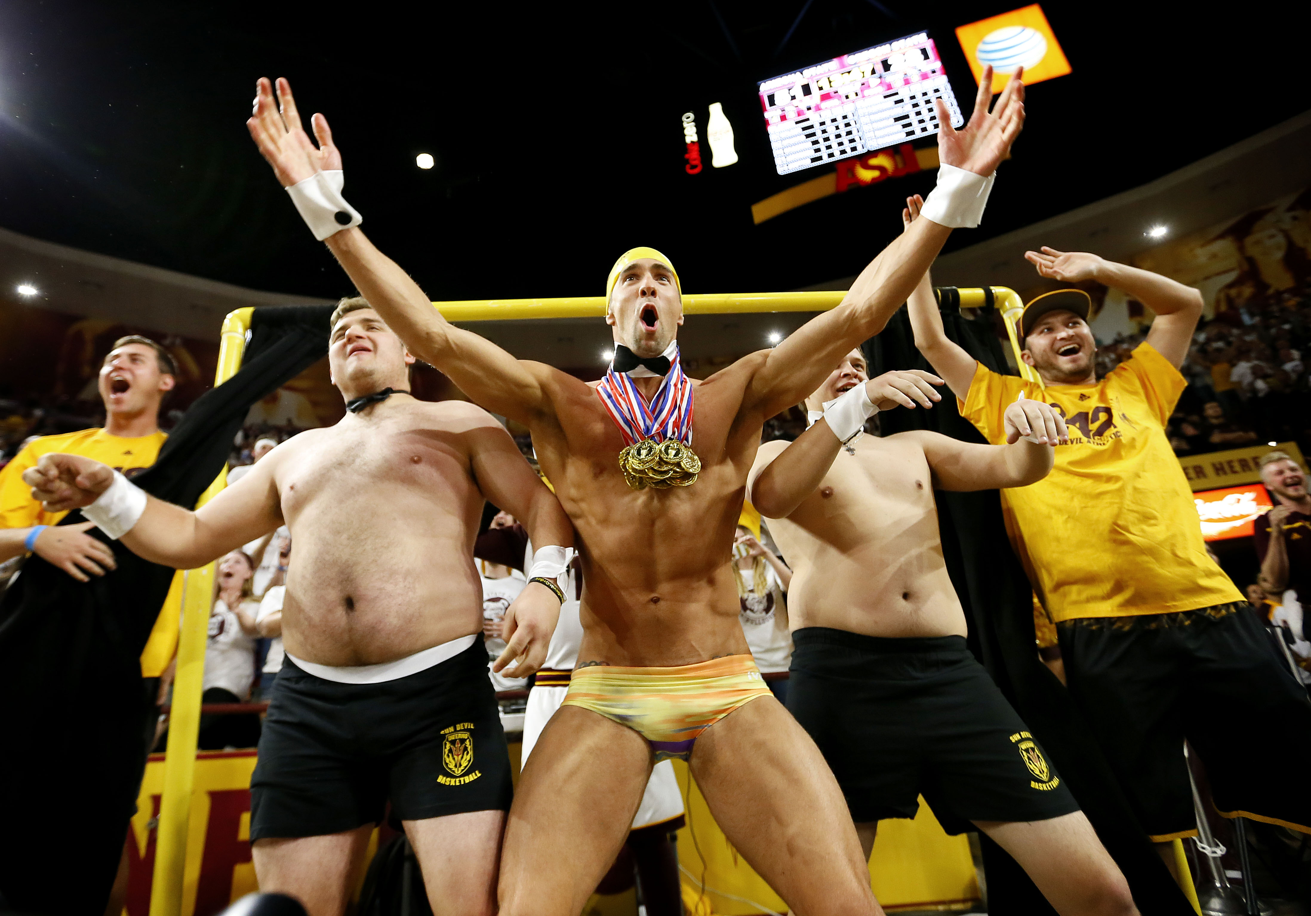 "Olympic swimmer Michael Phelps, center, performs behind the ""Curtain of Distraction"" during an Oregon State free throw against Arizona State in the second half of an NCAA college basketball game, Thursday, Jan. 28, 2016, in Tempe, Ariz. (AP Photo/Matt Yor"