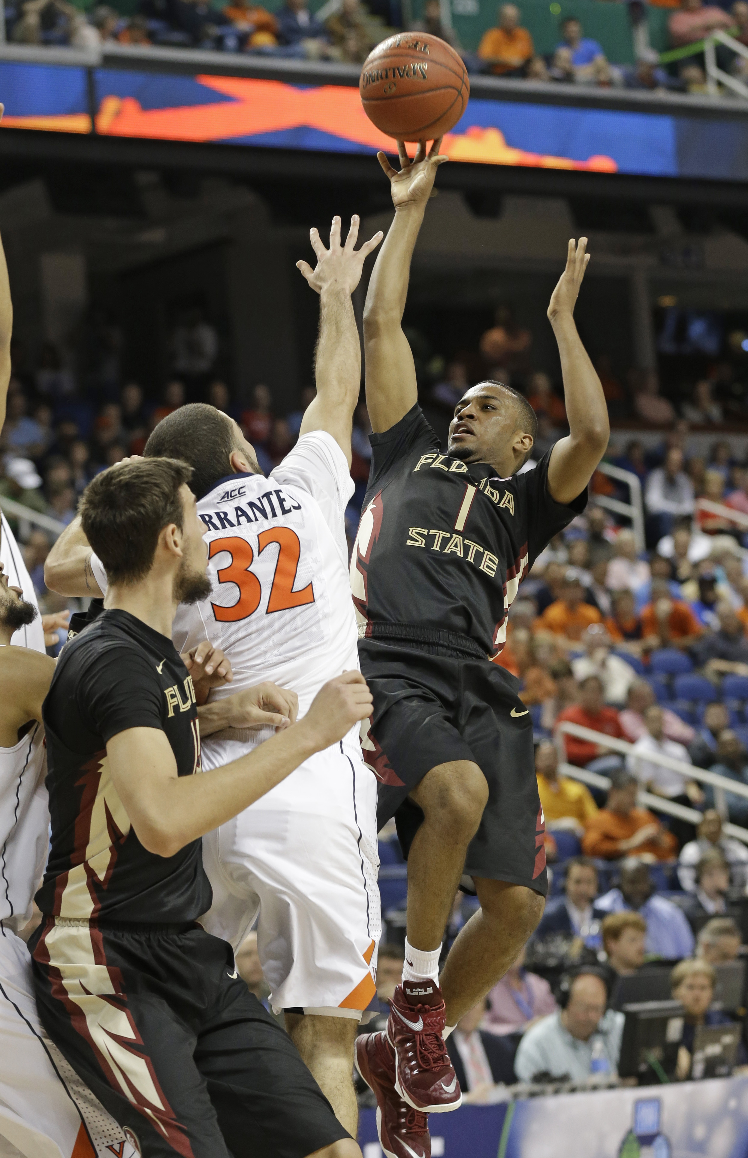 FILE- In this March 12, 2015, file photo, Florida State's Devon Bookert (1) shoots over Virginia's London Perrantes (32) during the second half of an NCAA college basketball game in the quarterfinals of the Atlantic Coast Conference tournament in Greensbo