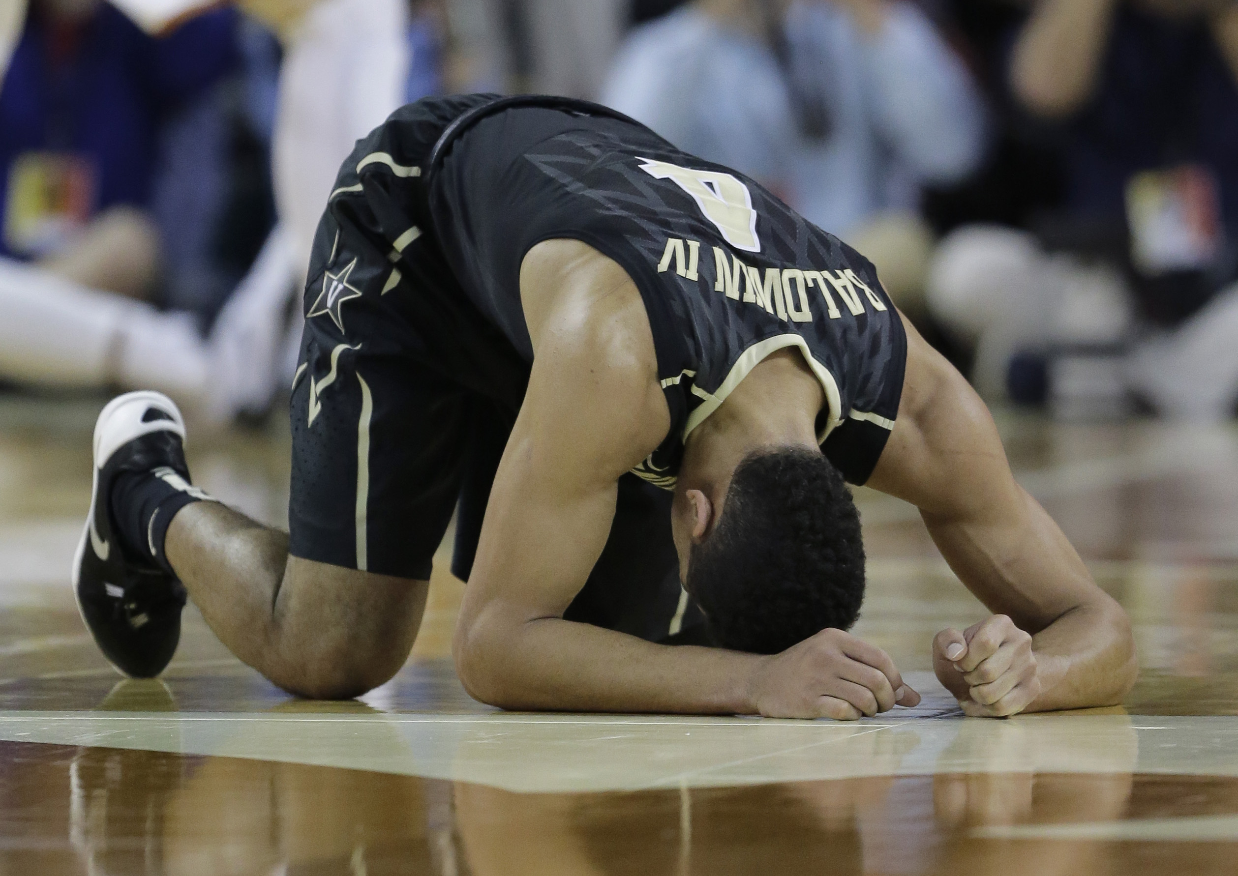 Vanderbilt guard Wade Baldwin IV (4) holds his head to the court after he was injured during the first half of an NCAA college basketball game against Texas, Saturday, Jan. 30, 2016, in Austin, Texas. (AP Photo/Eric Gay)