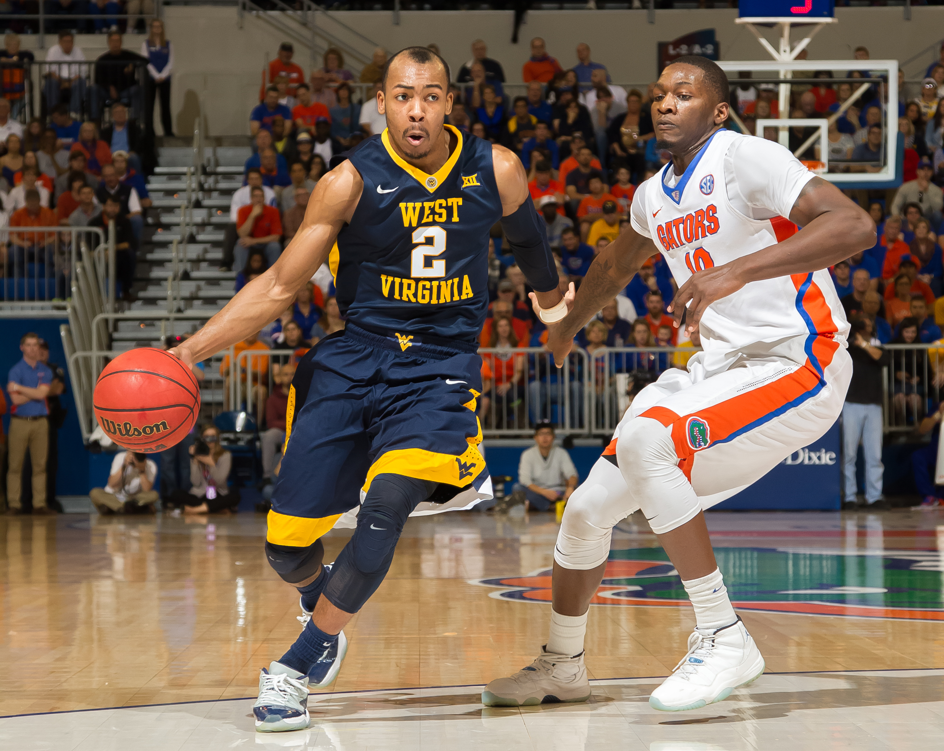 West Virginia guard Jevon Carter (2) dribbles past Florida forward Dorian Finney-Smith (10) during the first half of an NCAA college basketball game, Saturday, Jan. 30, 2016, in Gainesville, Fla. (AP Photo/Ronald Irby)
