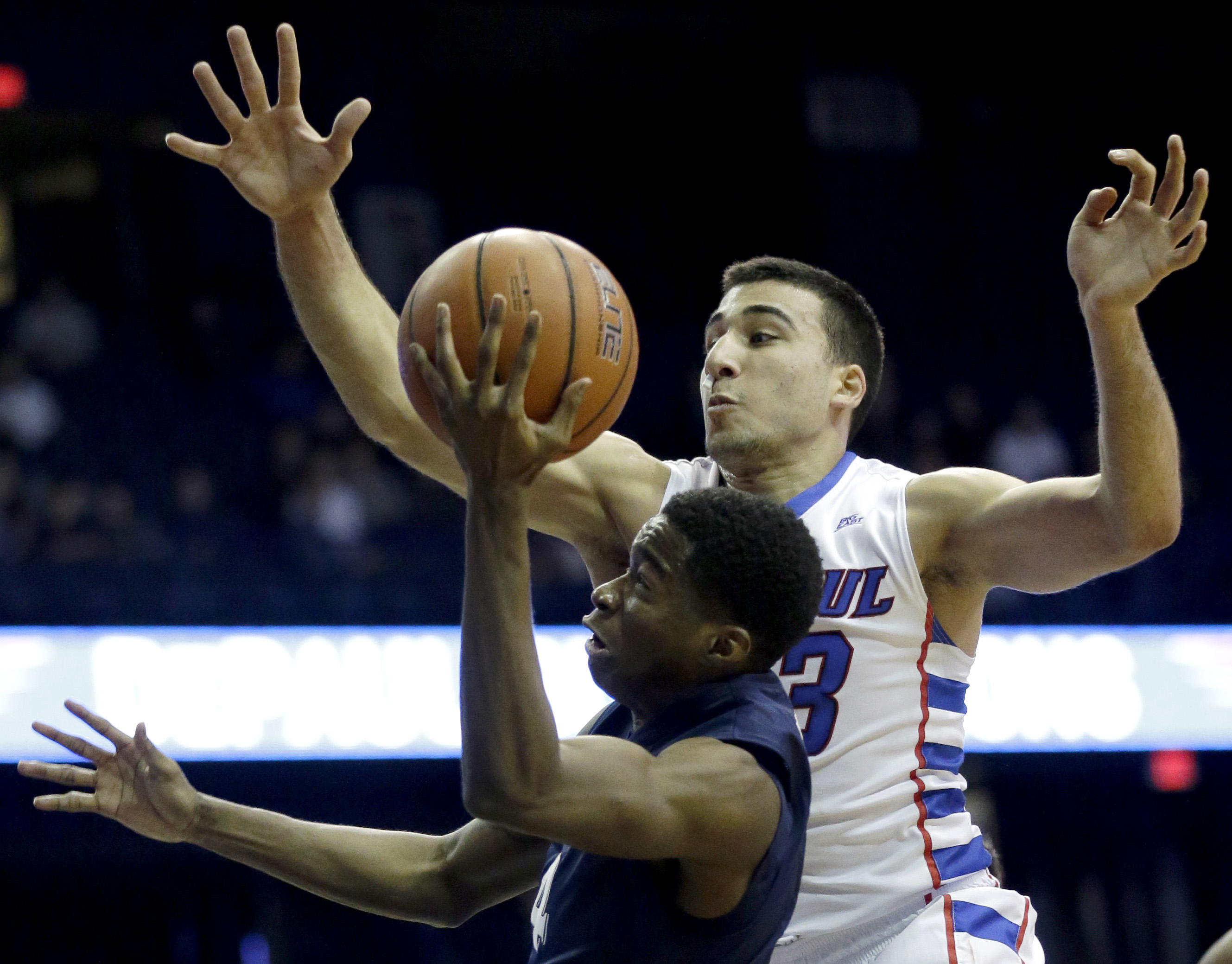Xavier guard Edmond Sumner, bottom, drives to the basket as DePaul guard Erten Gazi guards during the first half of an NCAA college basketball game Saturday, Jan. 30, 2016, in Rosemont, Ill. (AP Photo/Nam Y. Huh)