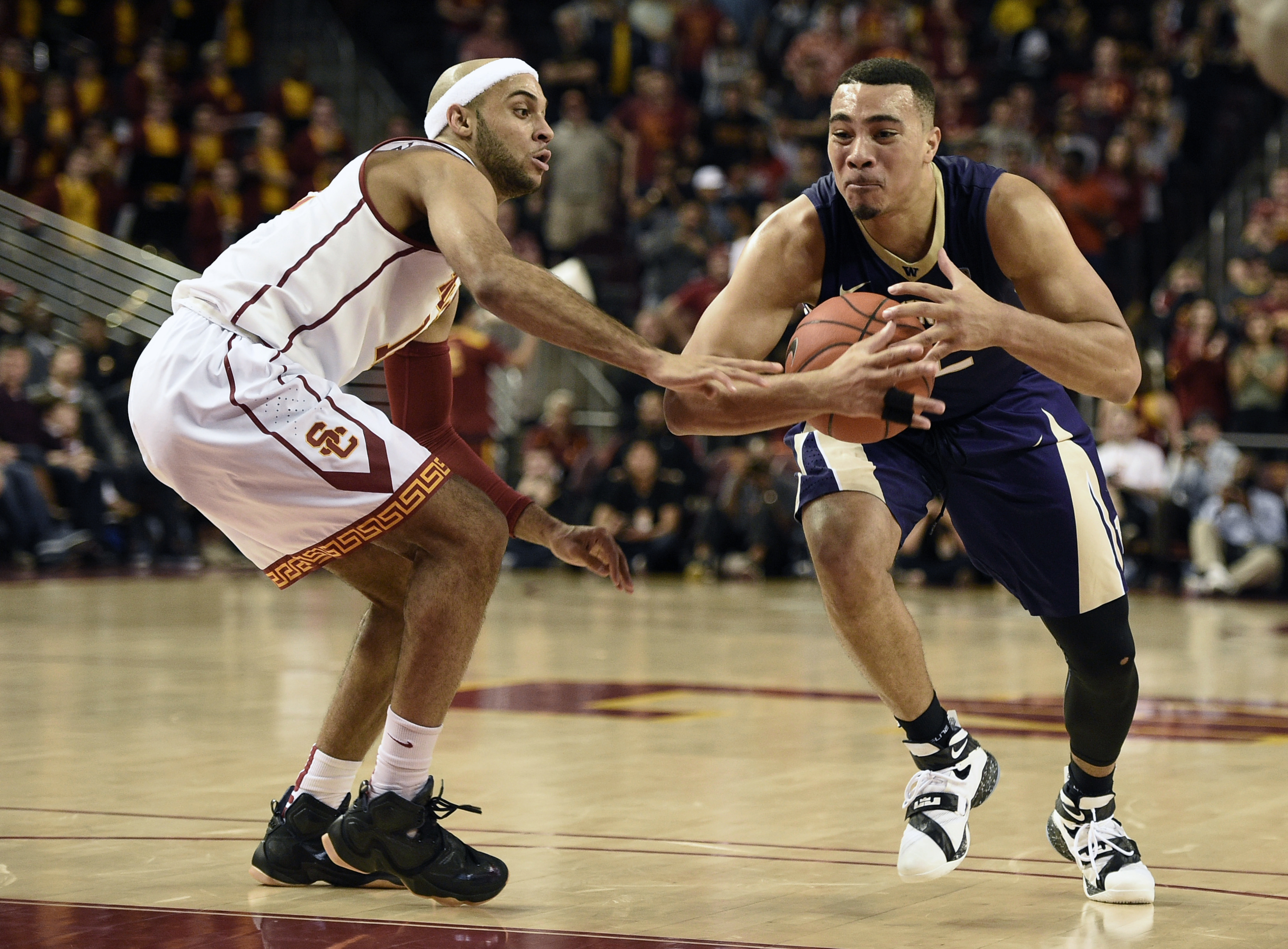 Washington guard Andrew Andrews, right, drives the ball by Southern California guard Julian Jacobs, left, during the first half of an NCAA college basketball game in Los Angeles, Saturday, Jan. 30, 2016. (AP Photo/Kelvin Kuo)