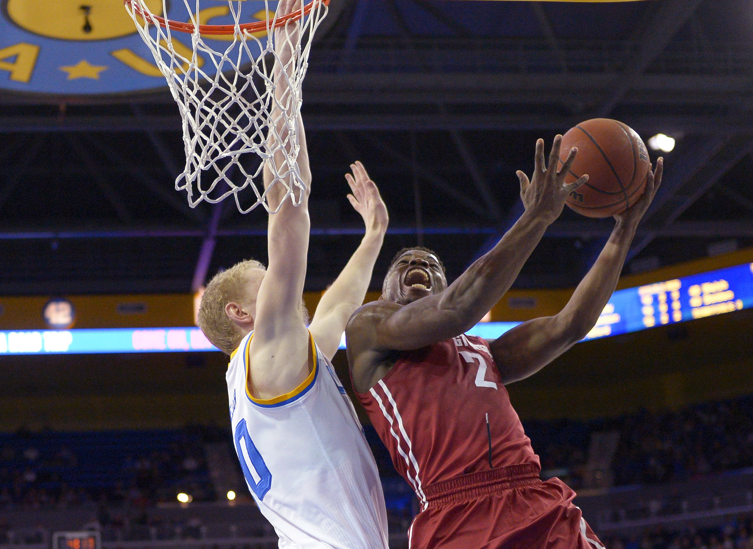 Washington State guard Ike Iroegbu, right, shoots as UCLA center Thomas Welsh defends during the second half of an NCAA college basketball game Saturday, Jan. 30, 2016, in Los Angeles. UCLA won 83-50. (AP Photo/Mark J. Terrill)
