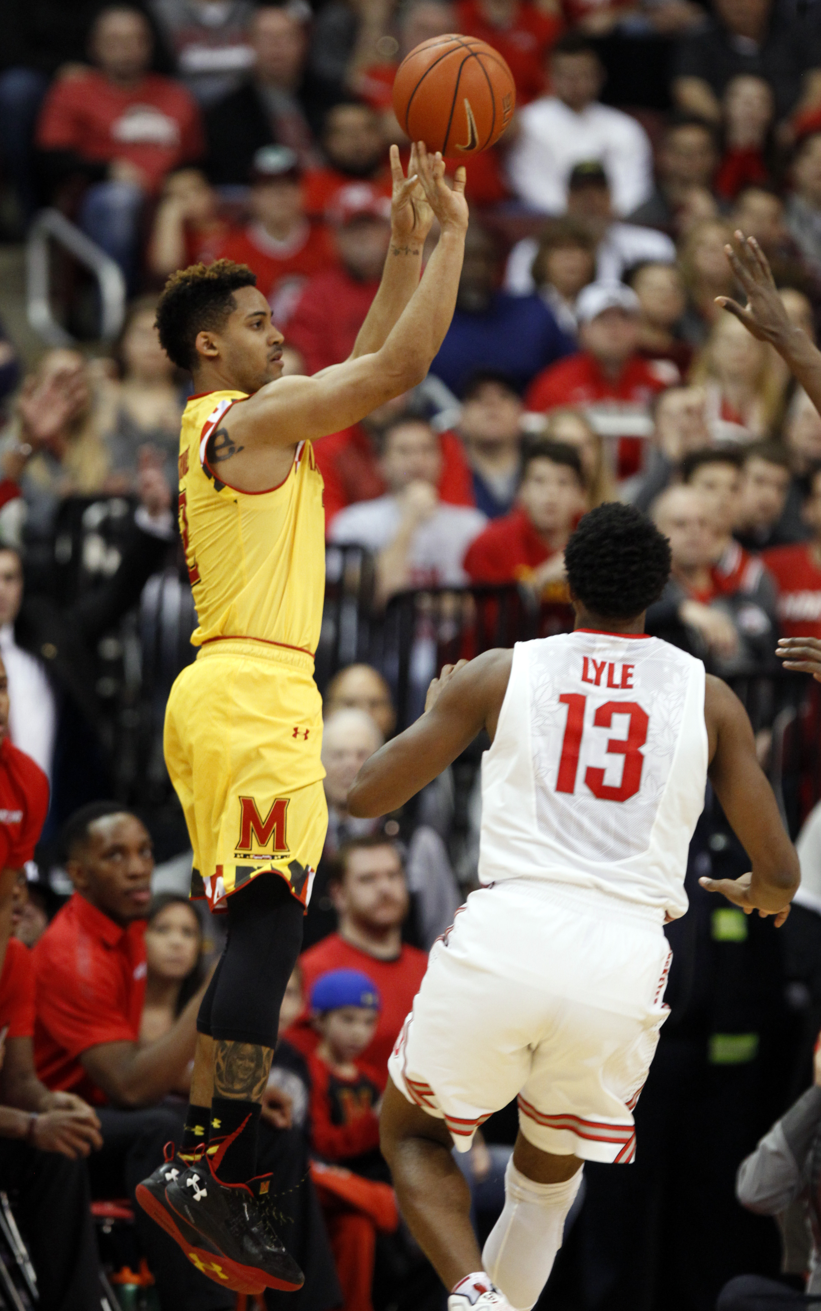 Maryland's Melo Trimble, left, goes up to shoot over Ohio State's JaQuan Lyle during the second half of an NCAA college basketball game in Columbus, Ohio, Sunday, Jan. 31, 2016. Maryland won 66-61. (AP Photo/Paul Vernon)