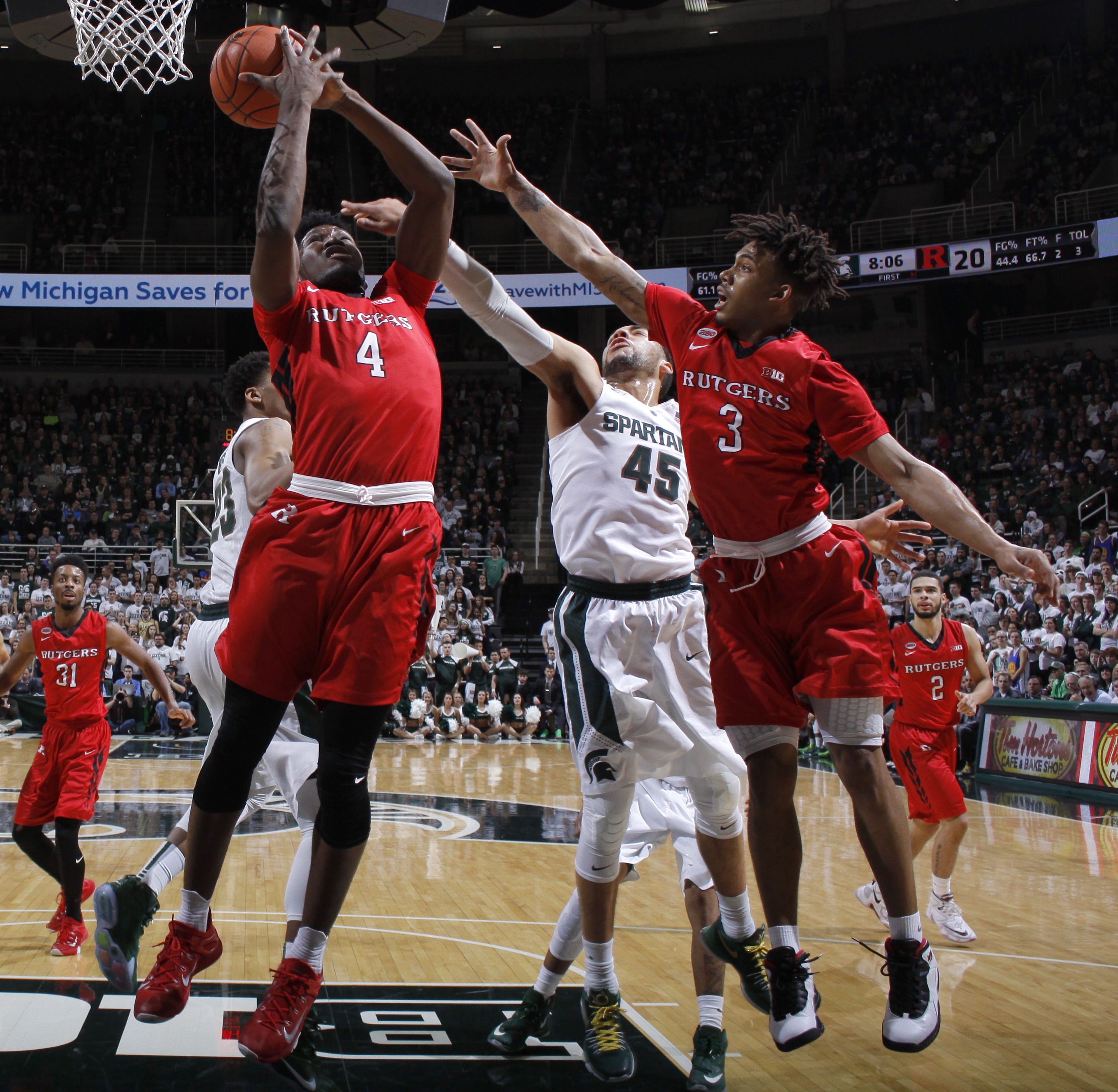 Rutgers' Jonathan Laurent (4) and Corey Sanders (3) and Michigan State's Denzel Valentine (45) reach for a rebound during the first half of an NCAA college basketball game, Sunday, Jan. 31, 2016, in East Lansing, Mich. (AP Photo/Al Goldis)