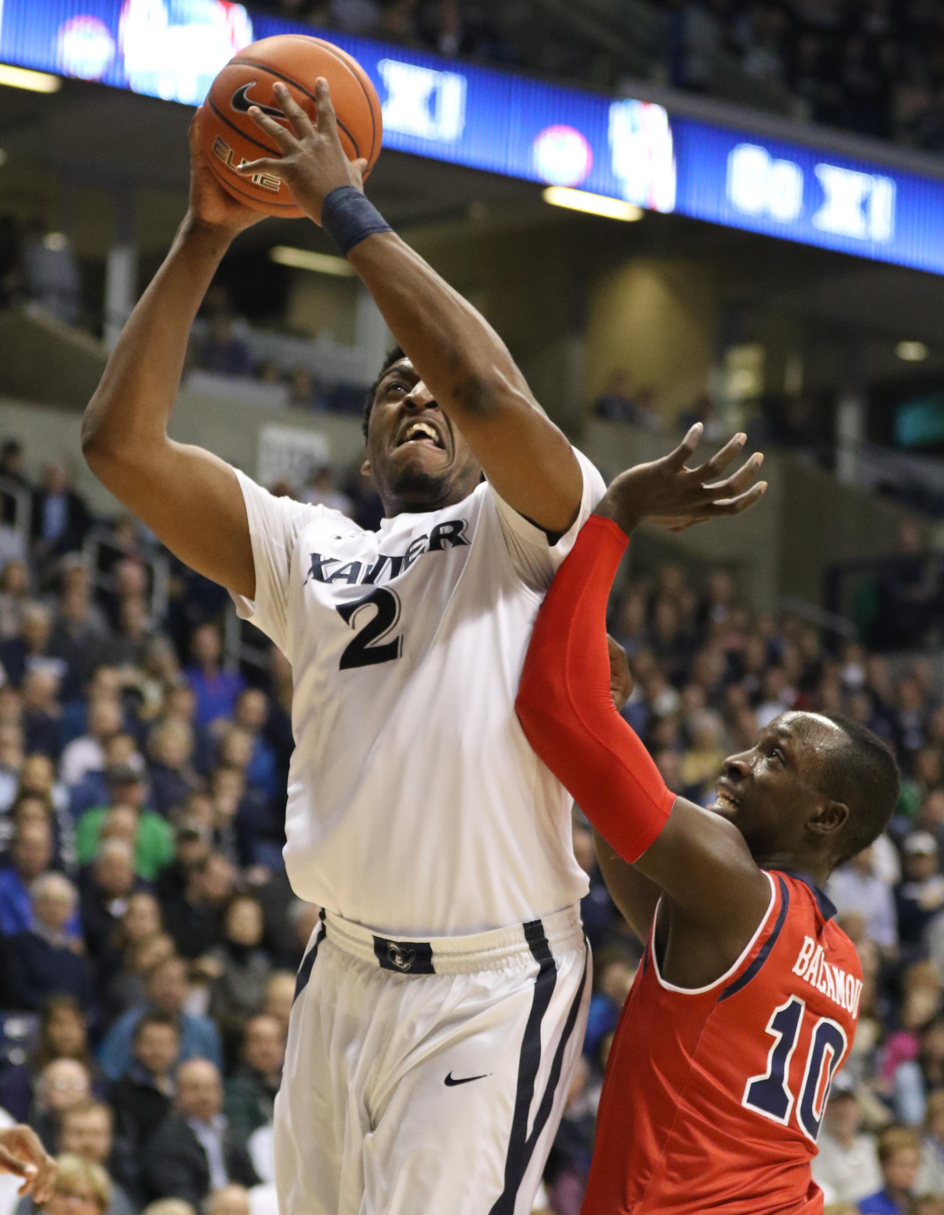 Xavier forward James Farr (2) puts up a shot against St. John's guard Felix Balamou (10) during the first half of an NCAA college basketball game Wednesday, Feb. 3, 2016, in Cincinnati. (AP Photo/Gary Landers)