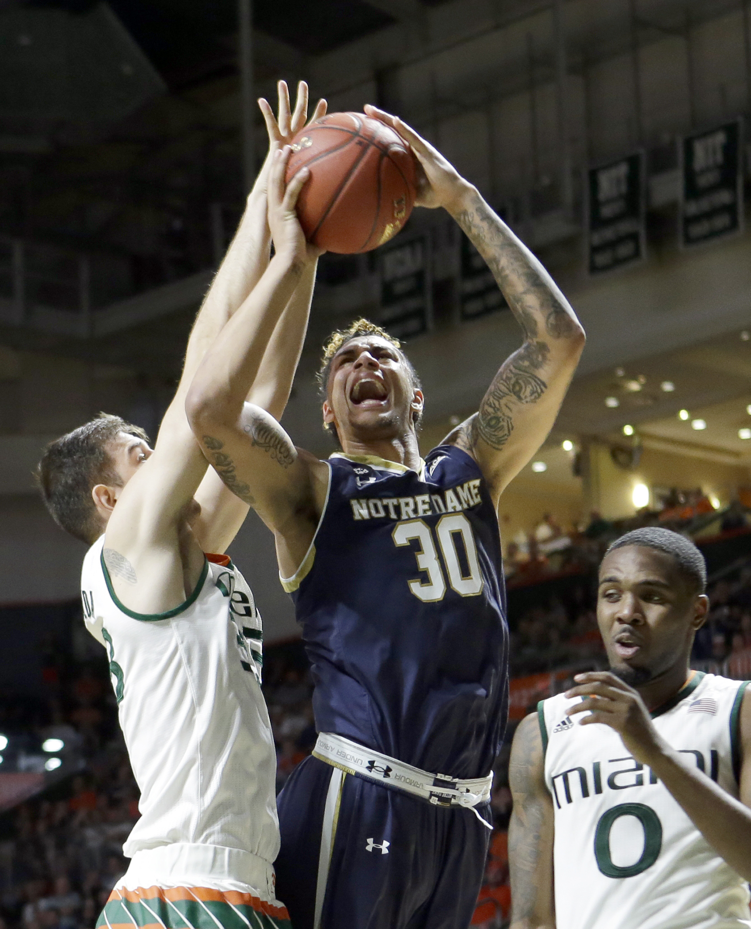Notre Dame forward Zach Auguste (30) is fouled by as he goes to the basket by Miami forward Ivan Cruz Uceda, left, in the second half of an NCAA college basketball game, Wednesday, Feb.3, 2016, Coral Gables, Fla. Miami won 79-70. (AP Photo/Alan Diaz)