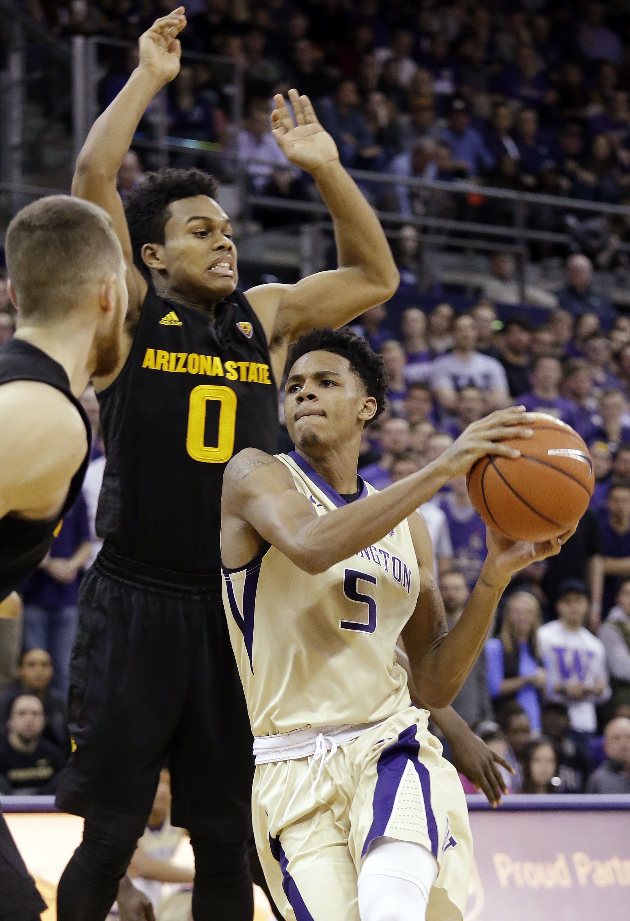 Washington's Dejounte Murray (5) drives past Arizona State's Tra Holder during the second half of an NCAA college basketball game Wednesday, Feb. 3, 2016, in Seattle. (AP Photo/Elaine Thompson)