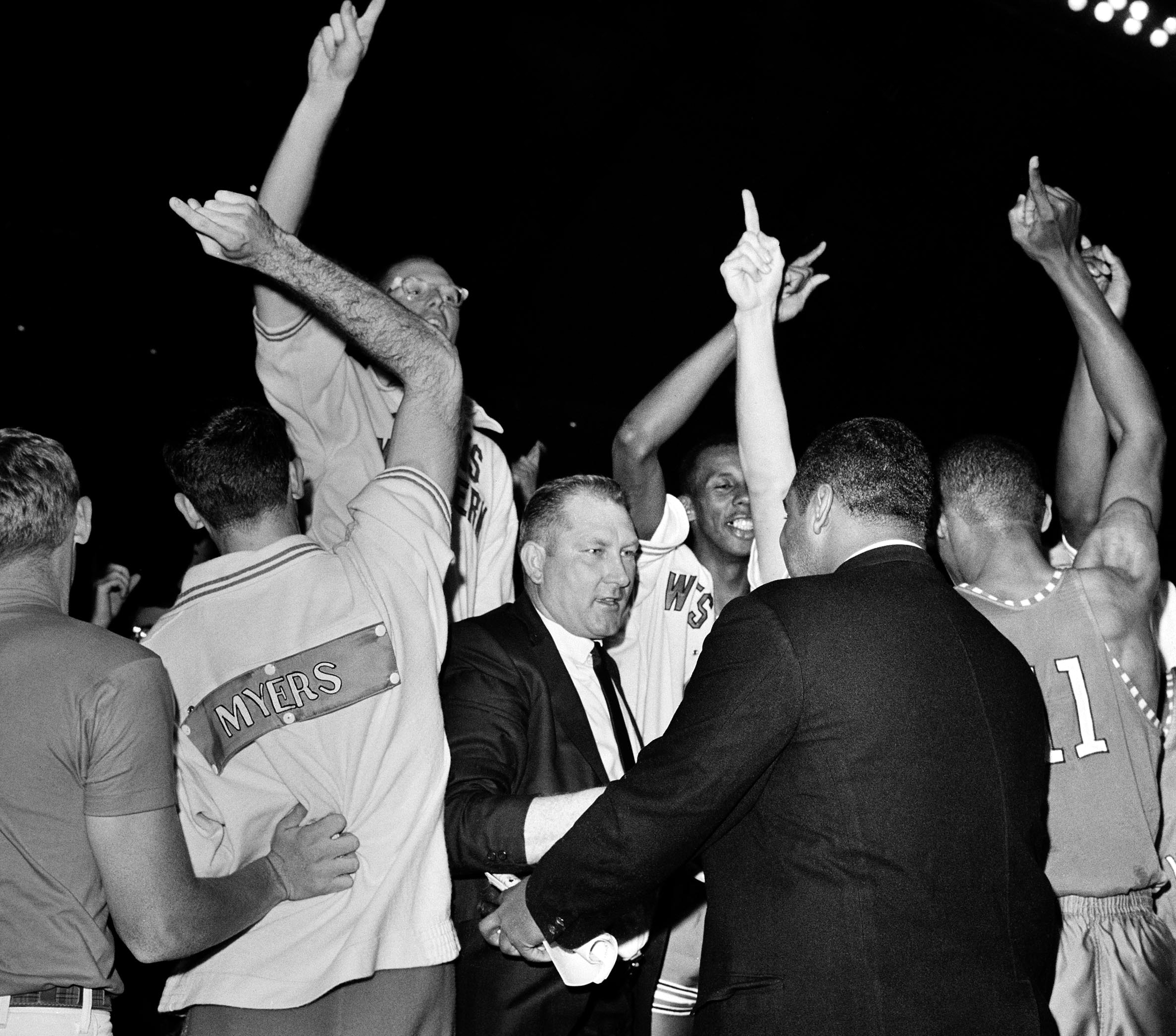 FILE - In this March 19, 1996, file photo, Don Haskins, center, coach of Texas Western, receives congratulations as his team is awarded the new National Collegiate Basketball championship in College Park, Md. Players from Texas Western's 1966 NCAA champio