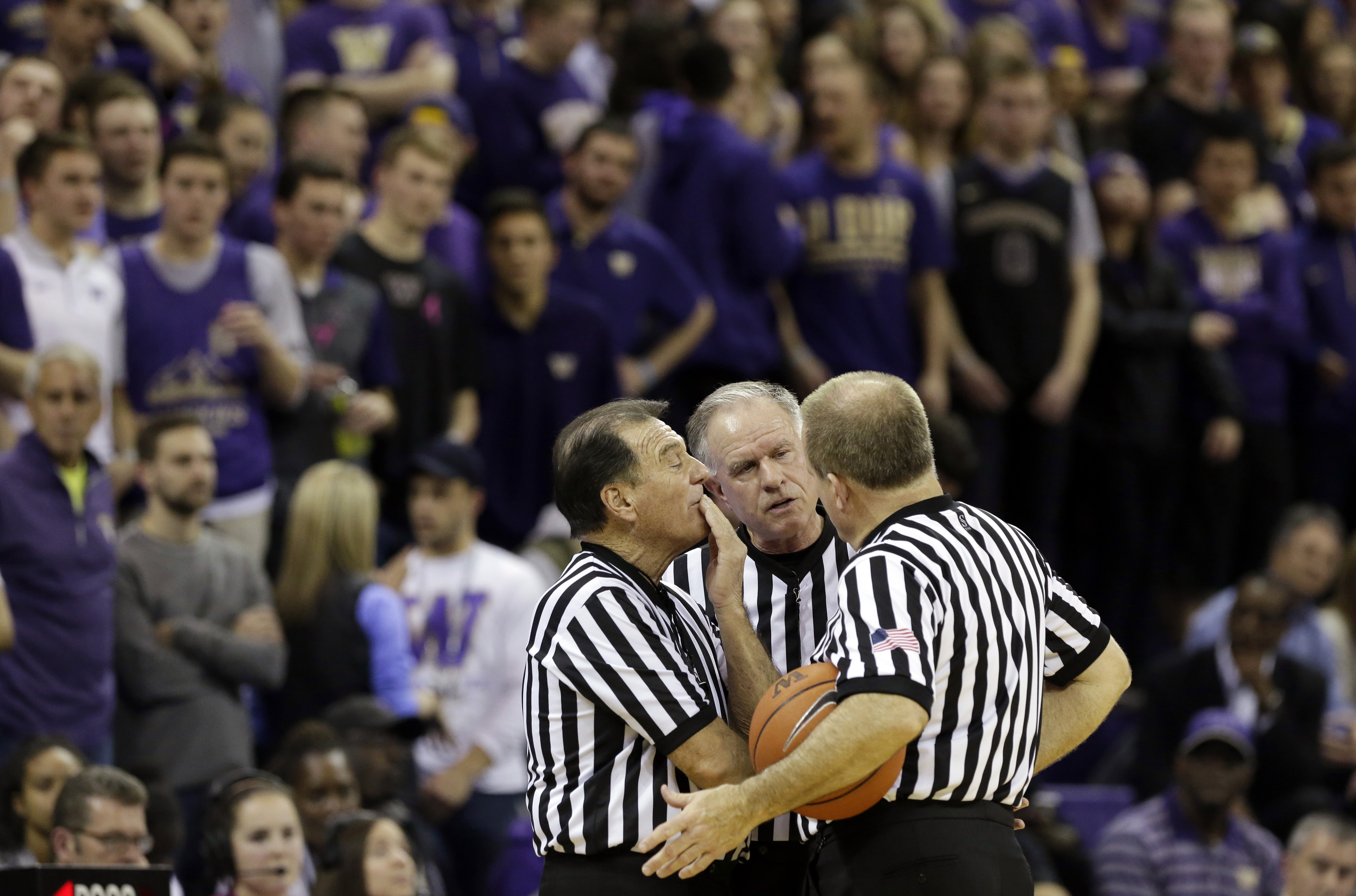 FILE - In this Wednesday Feb. 3, 2016, file photo, officials discuss a call between Washington and Arizona State during the second half of an NCAA college basketball game in Seattle. Referees undergo nearly as much scrutiny as the teams that want to join