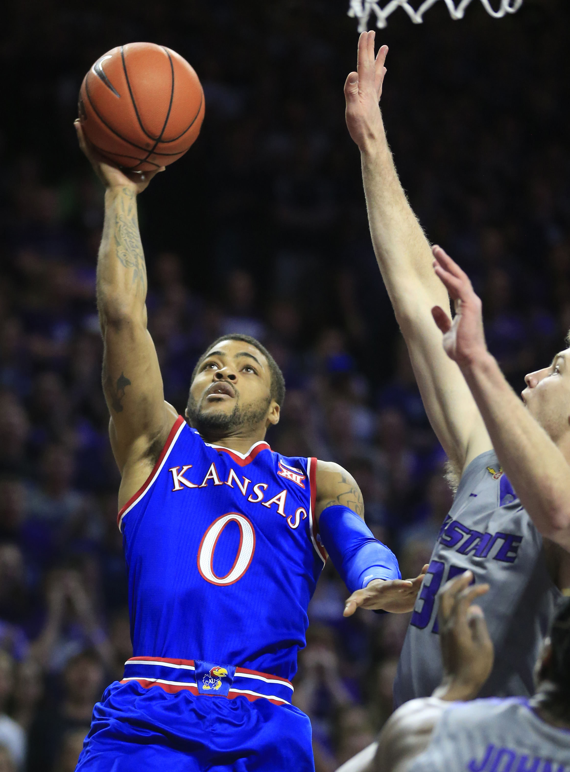 Kansas guard Frank Mason III (0) shoots as Kansas State forward Dean Wade (32) defends during the first half of an NCAA college basketball game in Manhattan, Kan., Saturday, Feb. 20, 2016. (AP Photo/Orlin Wagner)
