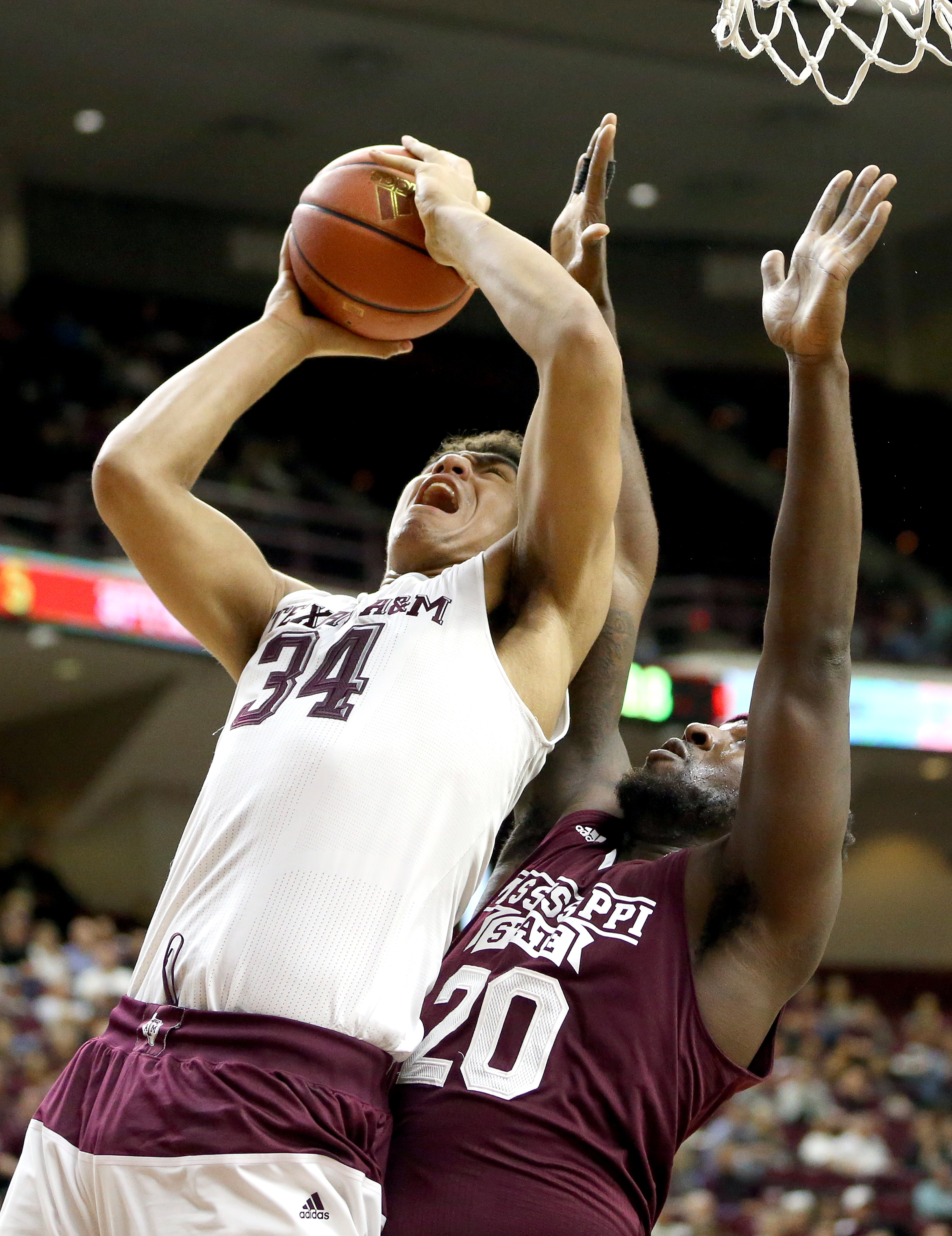Texas A&M's Tyler Davis (34) makes a basket as Mississippi State's Gavin Ware (20) during the first half of an NCAA college basketball game, Wednesday, Feb. 24, 2016, in College Station, Texas.  (AP Photo/Sam Craft)