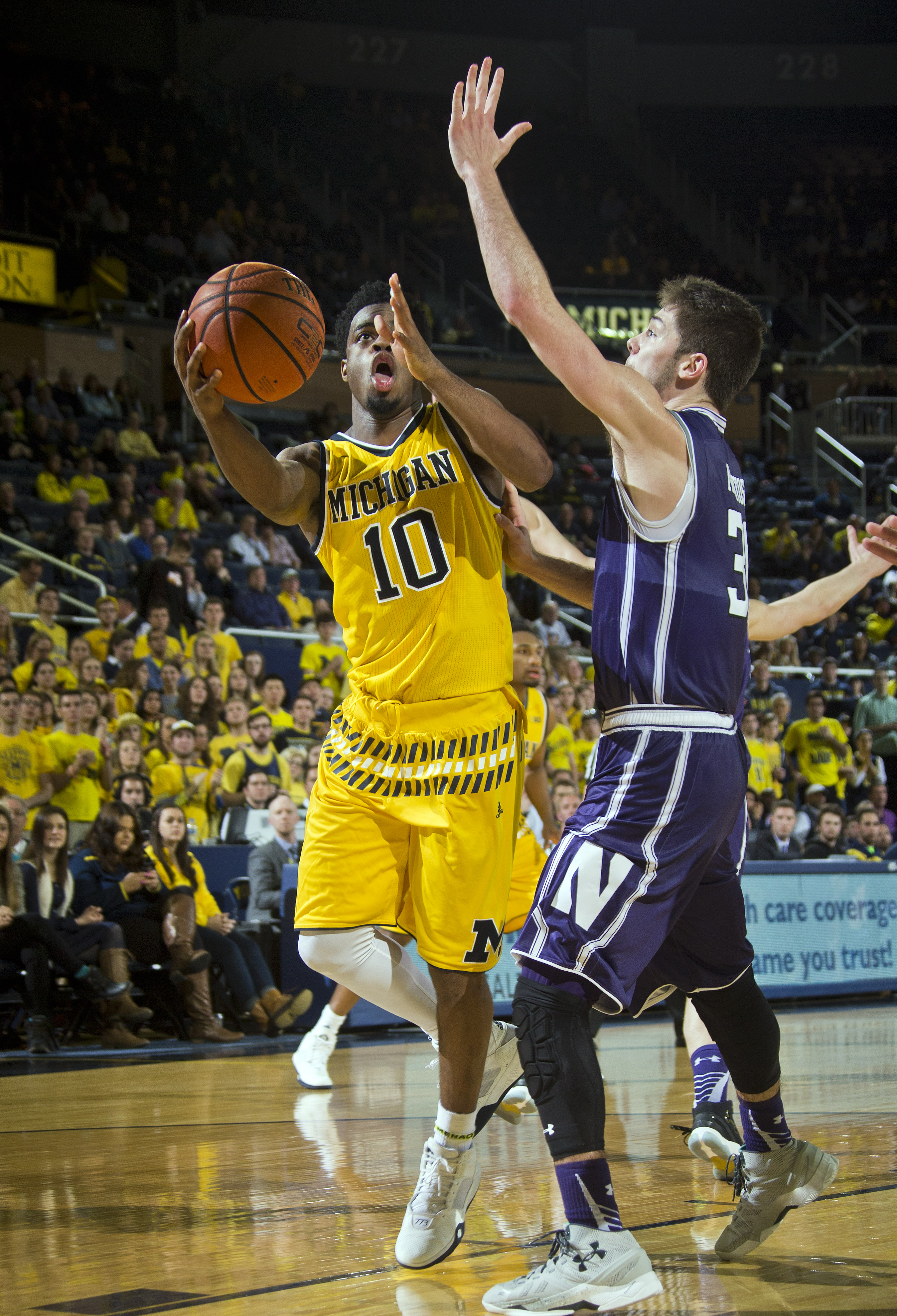 Michigan guard Derrick Walton Jr. (10) tries to go to the basket, defended by Northwestern guard Bryant McIntosh, right, in the second half of an NCAA college basketball game at Crisler Center in Ann Arbor, Mich., Wednesday, Feb. 24, 2016. Michigan won 72