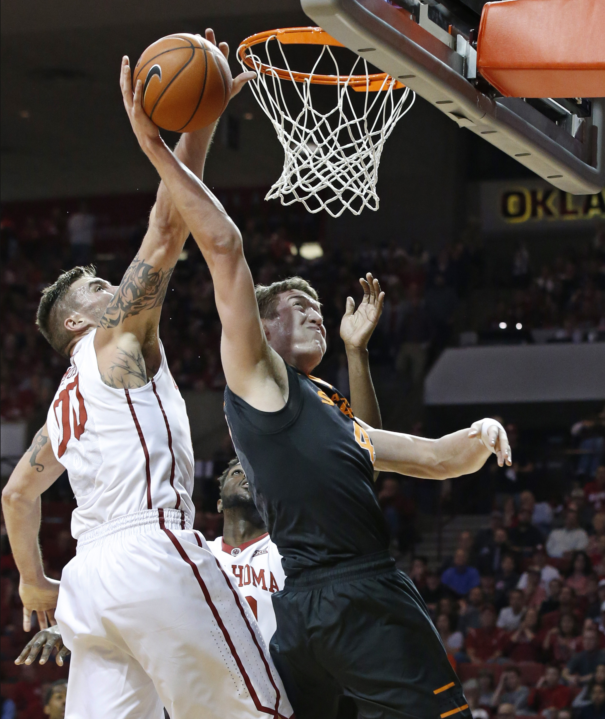 Oklahoma forward Ryan Spangler (00) blocks a shot by Oklahoma State forward Mitchell Solomon, right, during the first half of an NCAA college basketball game in Norman, Okla., Wednesday, Feb. 24, 2016. (AP Photo/Sue Ogrocki)