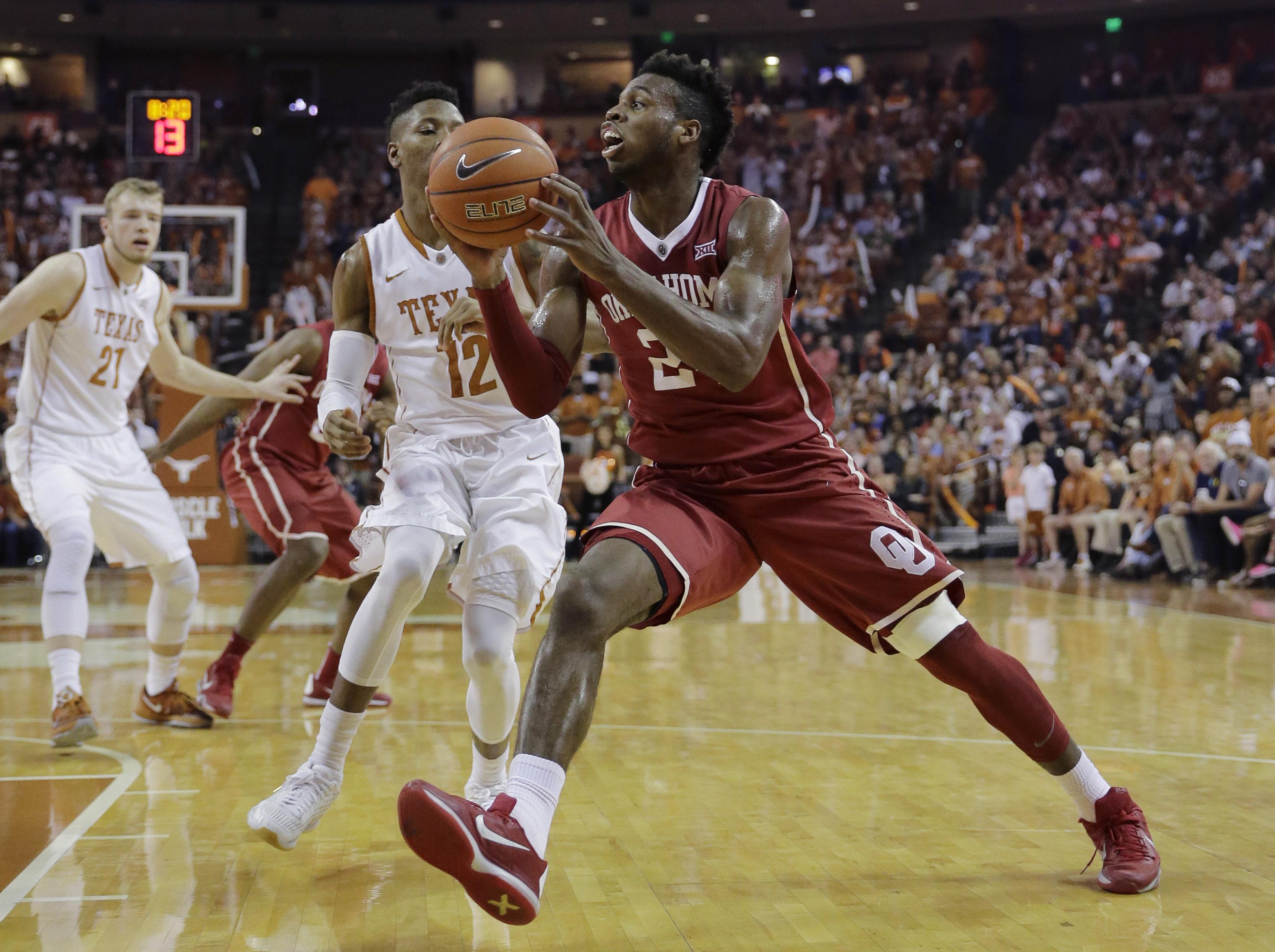Oklahoma forward Khadeem Lattin (12) drives the ball around Texas guard Kerwin Roach Jr. (12) during the first half of an NCAA college basketball game, Saturday, Feb. 27, 2016, in Austin, Texas. (AP Photo/Eric Gay)