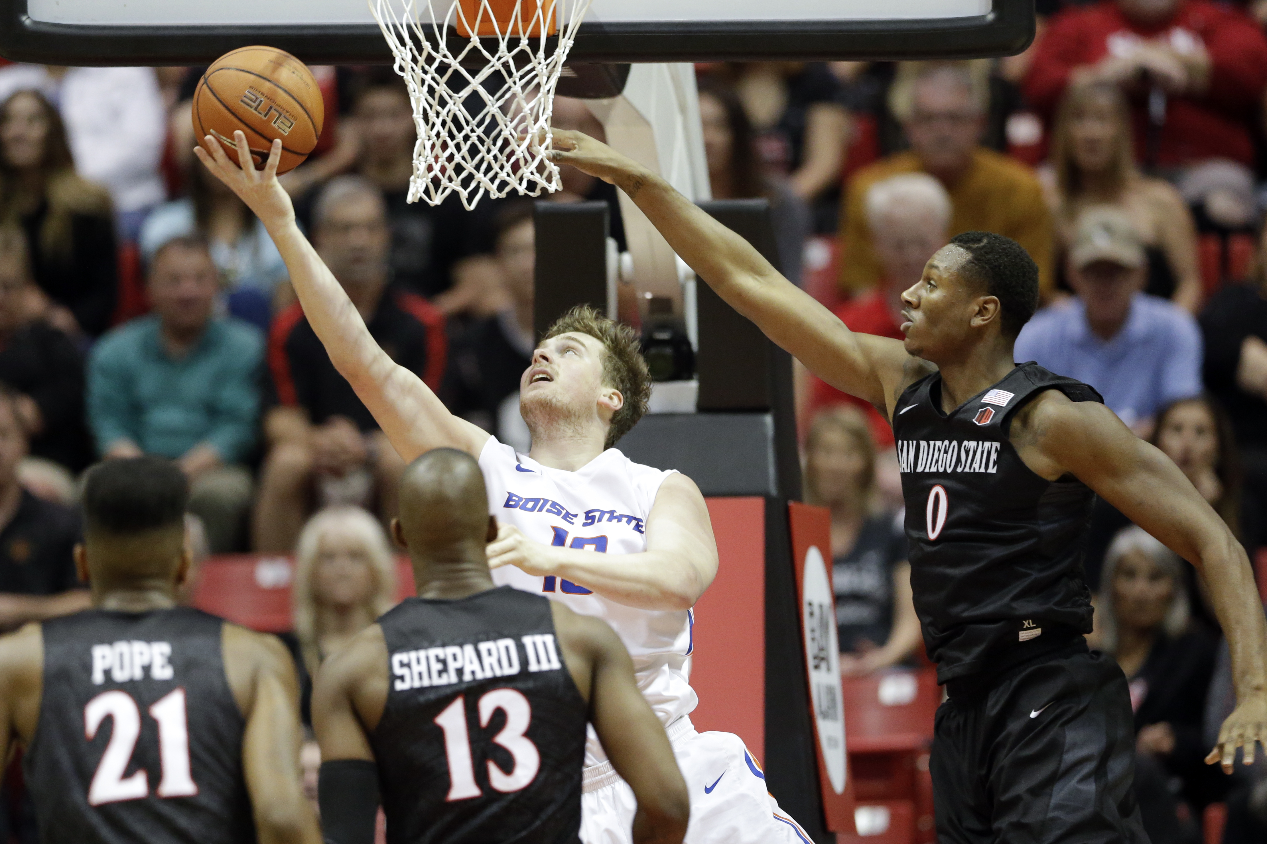 Boise State forward Nick Duncan, center, shoots past San Diego State forward Skylar Spencer (0) during the first half of an NCAA college basketball game Saturday, Feb. 27, 2016, in San Diego. (AP Photo/Gregory Bull)