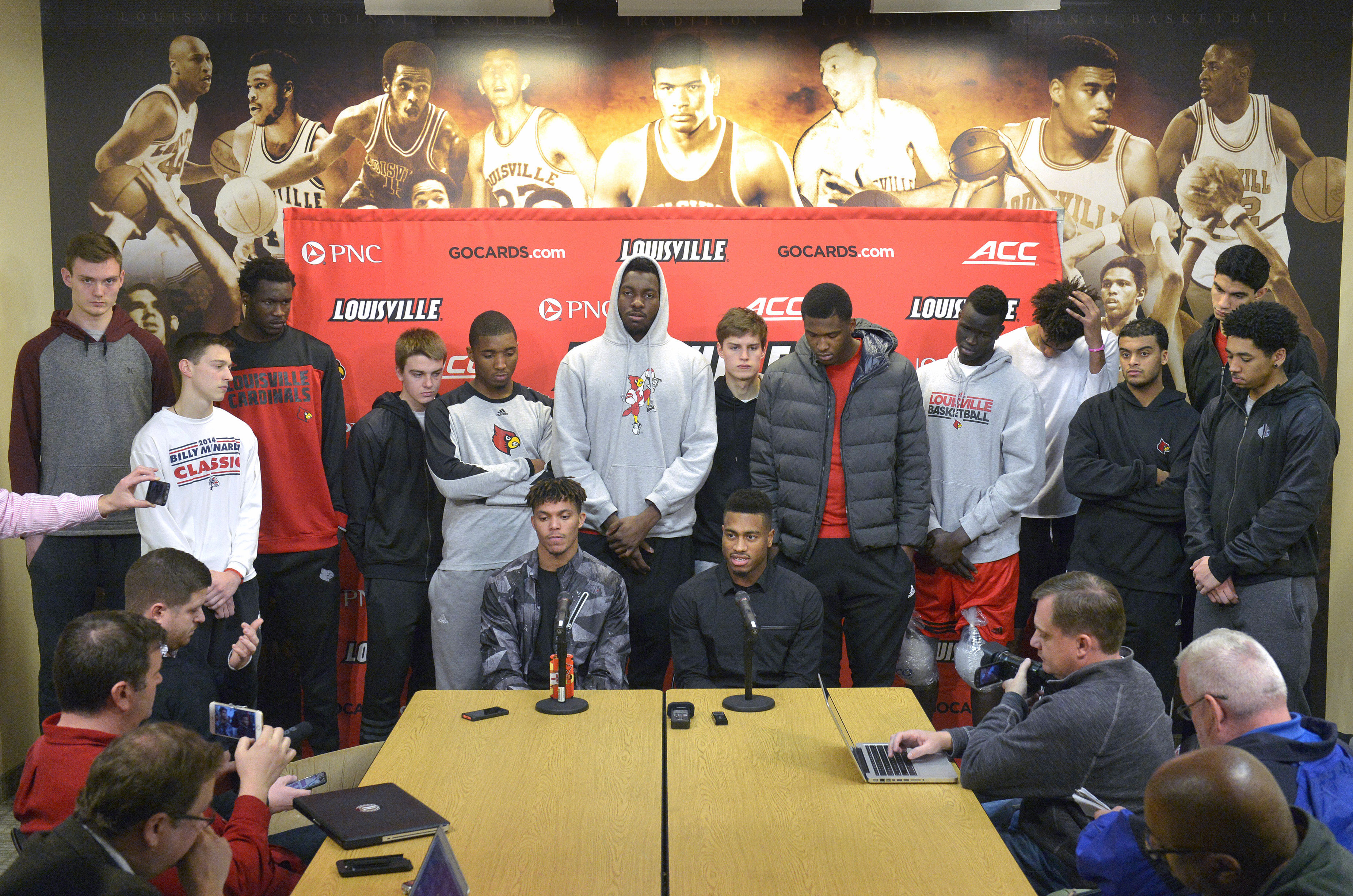 FILE - In this Feb. 5, 2016, file photo, surrounded by teammates, Louisville graduate students Damion Lee, seated left, and Trey Lewis meet with reporters during a press conference, in Louisville Ky. Louisville's decision to sit out the postseason because