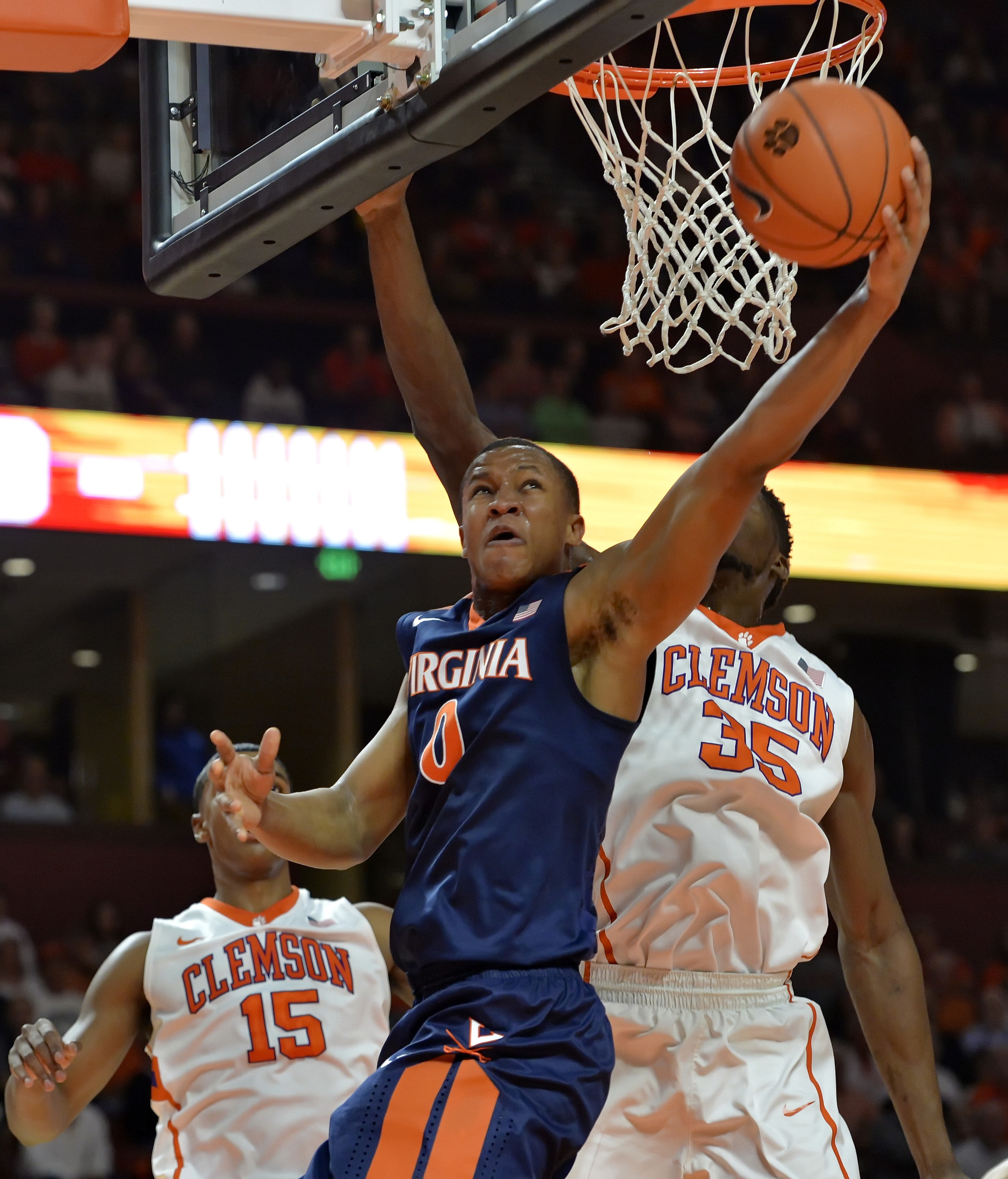 Virginia's Devon Hall drives in for a layup while defended by Clemson's Landry Nnoko, right, during the first half of an NCAA college basketball game Tuesday, March 1, 2016, in Greenville, S.C.  (AP Photo/Richard Shiro)