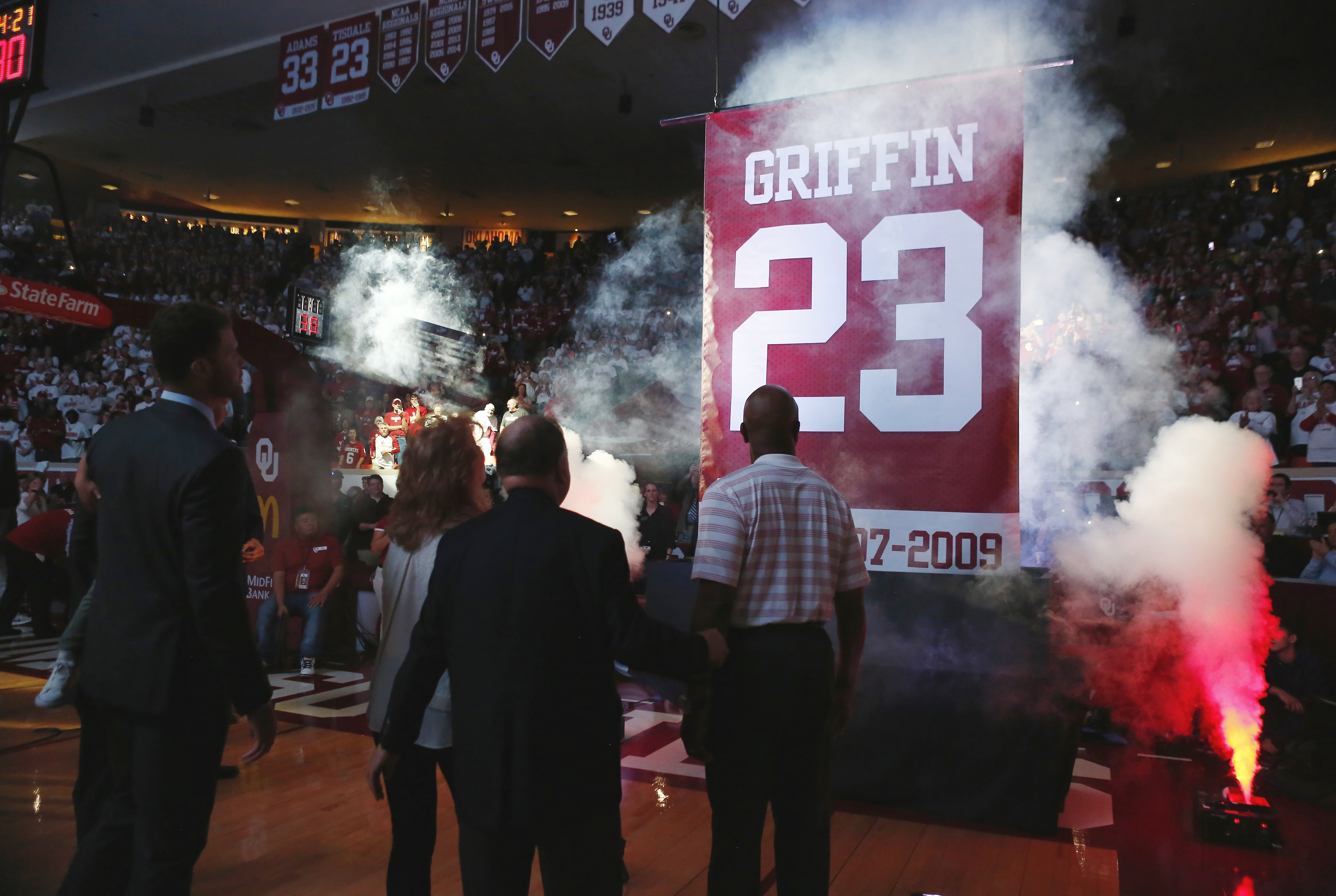 Los Angeles Clippers' Blake Griffin, left, and his family watch as his Oklahoma jersey number is retired during halftime of Oklahoma's NCAA college basketball game against Baylor in Norman, Okla., Tuesday, March 1, 2016. (AP Photo/Alonzo Adams)