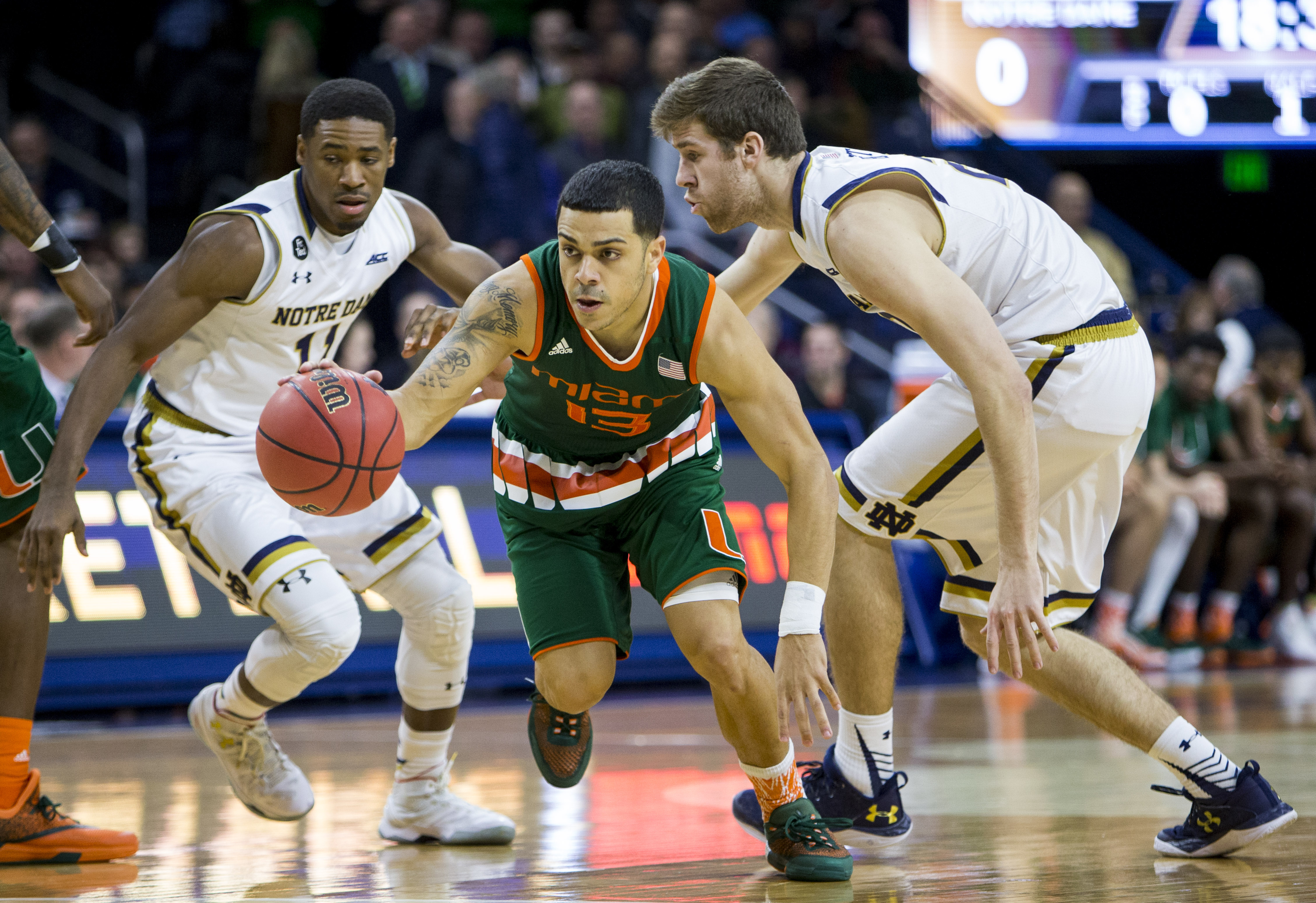 Miami's Angel Rodriguez (13) drives between Notre Dame's Demetrius Jackson (11) and A.J. Burgett, right, during the first half of an NCAA college basketball game Wednesday, March 2, 2016, in South Bend, Ind. (AP Photo/Robert Franklin)