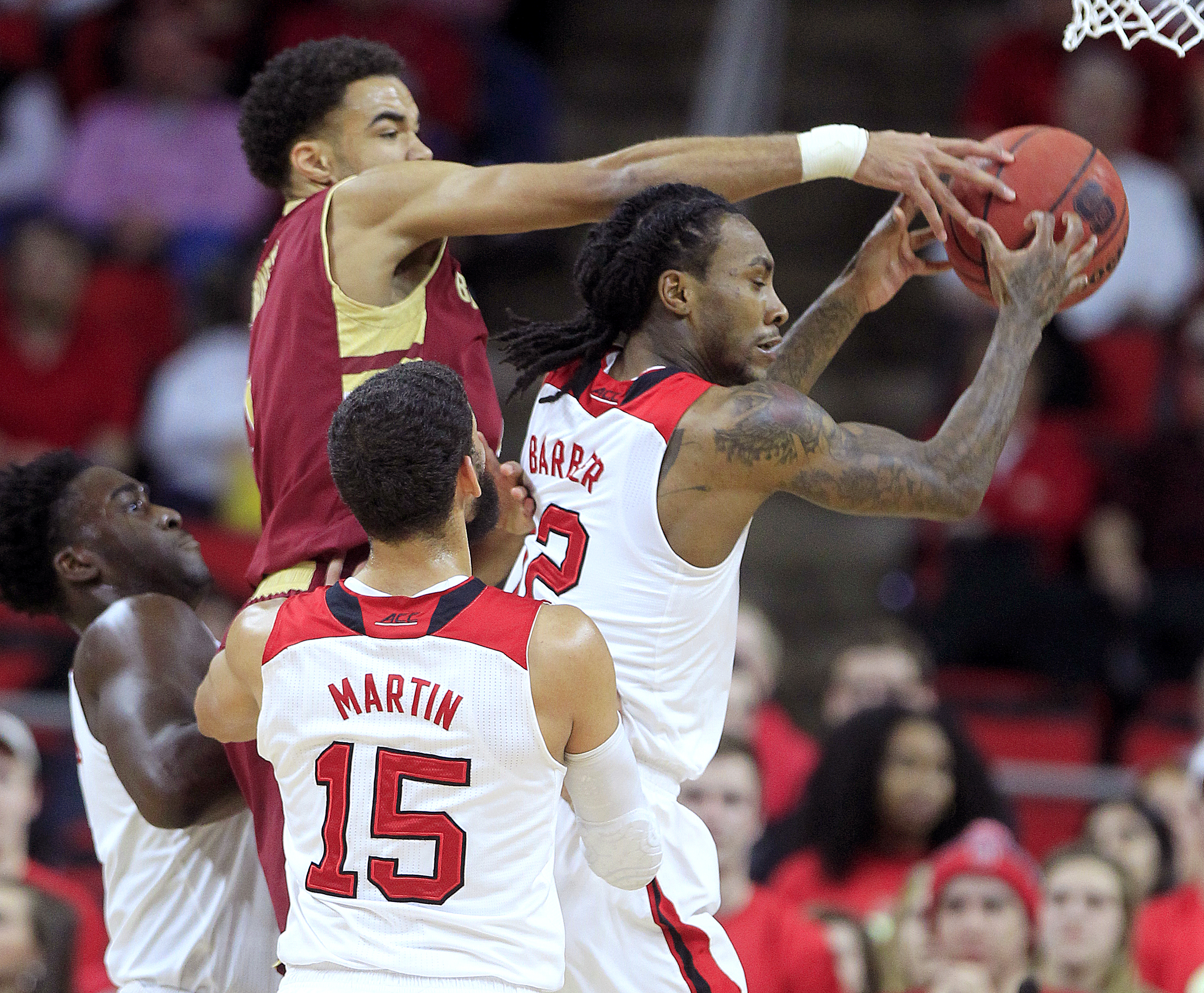 North Carolina State's Cat Barber (12) pulls in a rebound from Boston College's Jerome Robinson (1) during the first half of an NCAA basketball game, Wednesday, March 2, 2016 in Raleigh, N.C. (Ethan Hyman/The News & Observer via AP) MANDATORY CREDIT