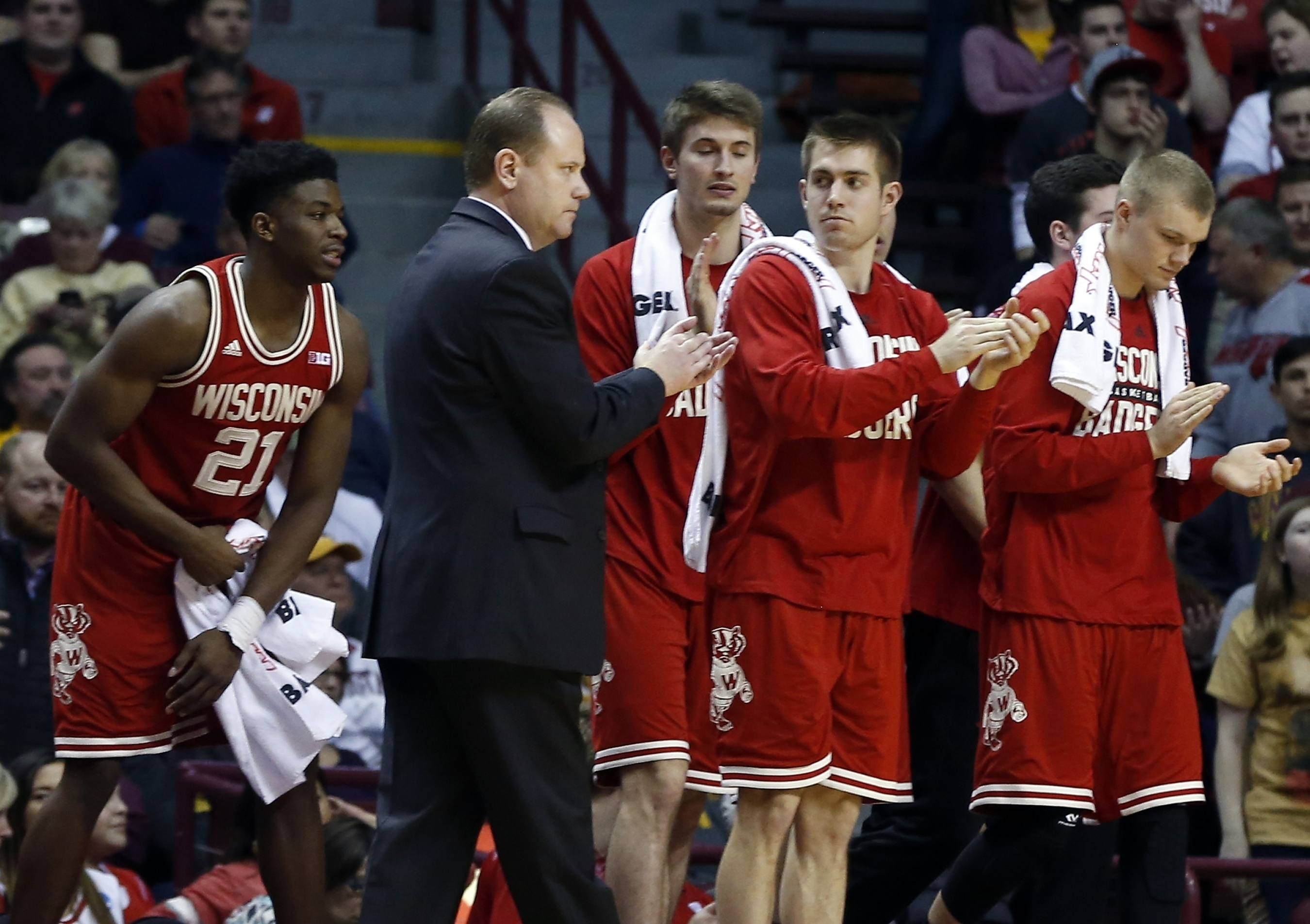 Wisconsin interi coach Greg Gard and his players applaud a play duirng the second half of an NCAA college basketball game against Minnesota, Wednesday, March 2, 2016, in Minneapolis. Wisconsin won 62-49. (AP Photo/Jim Mone)
