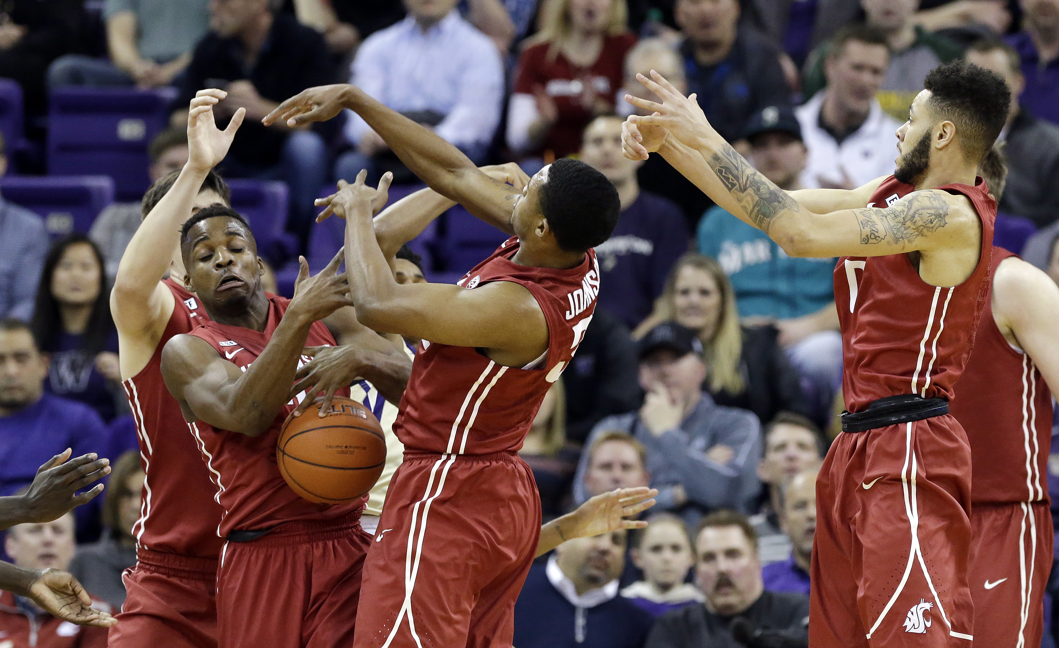 Washington State's Conor Clifford, left, Ike Iroegbu, Que Johnson and Derrien King all reach for a loose ball during the first half of an NCAA college basketball game against Washington on Wednesday, March 2, 2016, in Seattle. (AP Photo/Elaine Thompson)