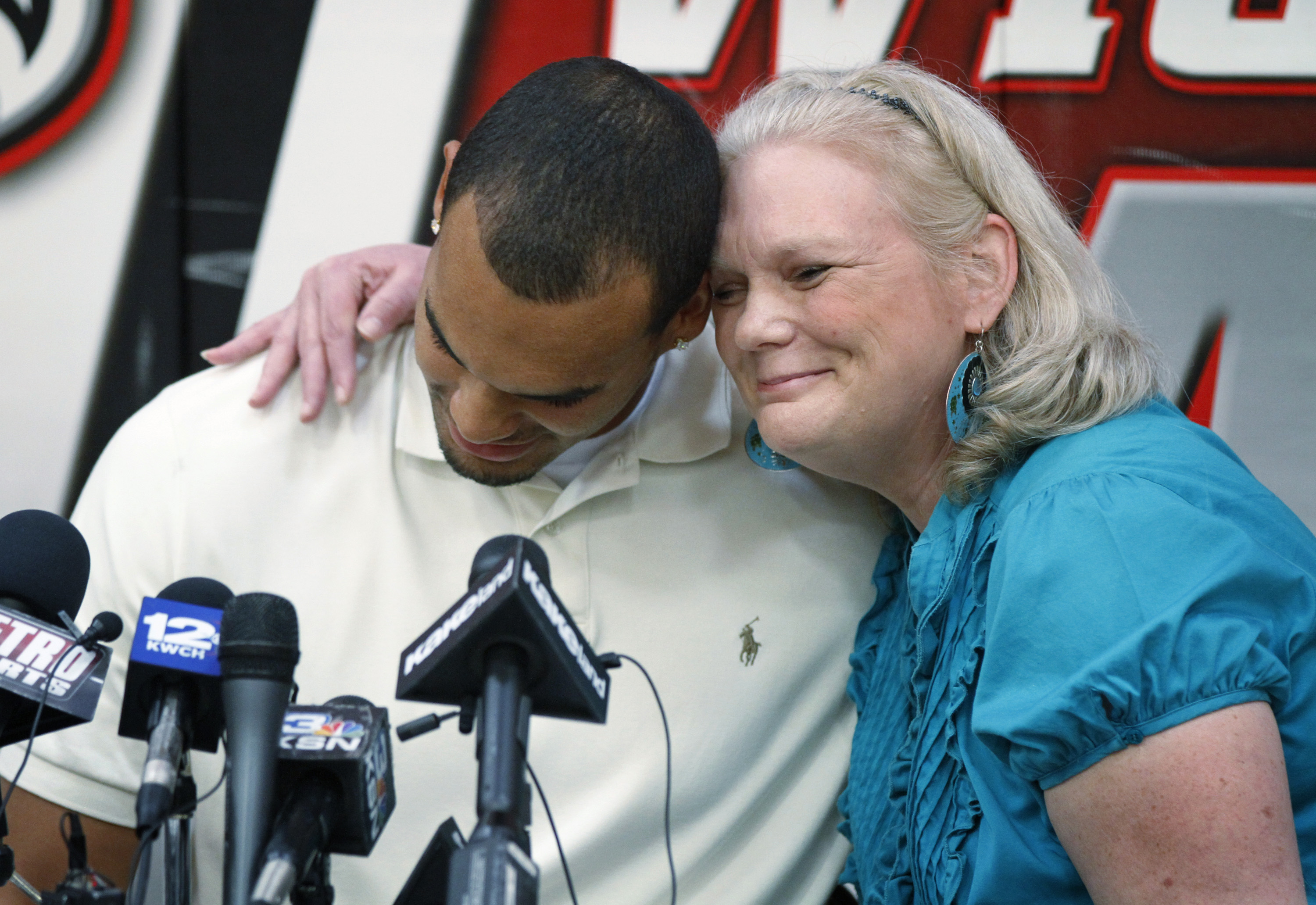 FILE - In this Sept. 21, 2011, file photo, Perry Ellis gets a hug from his mother, Fonda Ellis, after announcing his intention to play basketball at Kansas, during a news conference at Heights High School in Wichita. When Perry Ellis plays his final home