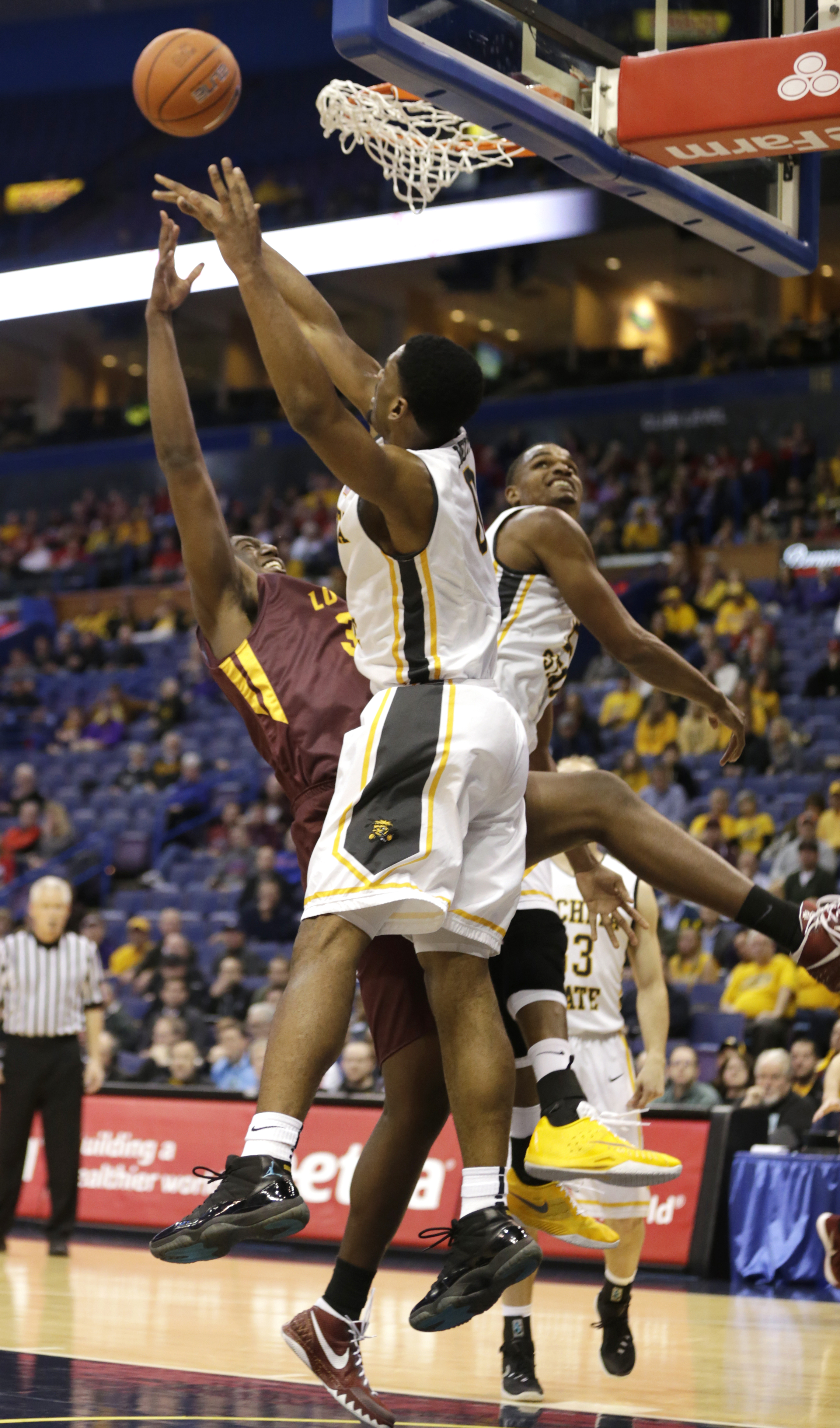 Wichita State's Rashard Kelly, center, slaps away a shot from Loyola's Milton Doyle, left, as Wichita State's Zach Brown defends during the first half of an NCAA college basketball game in the quarterfinals of the Missouri Valley Conference tournament, Fr