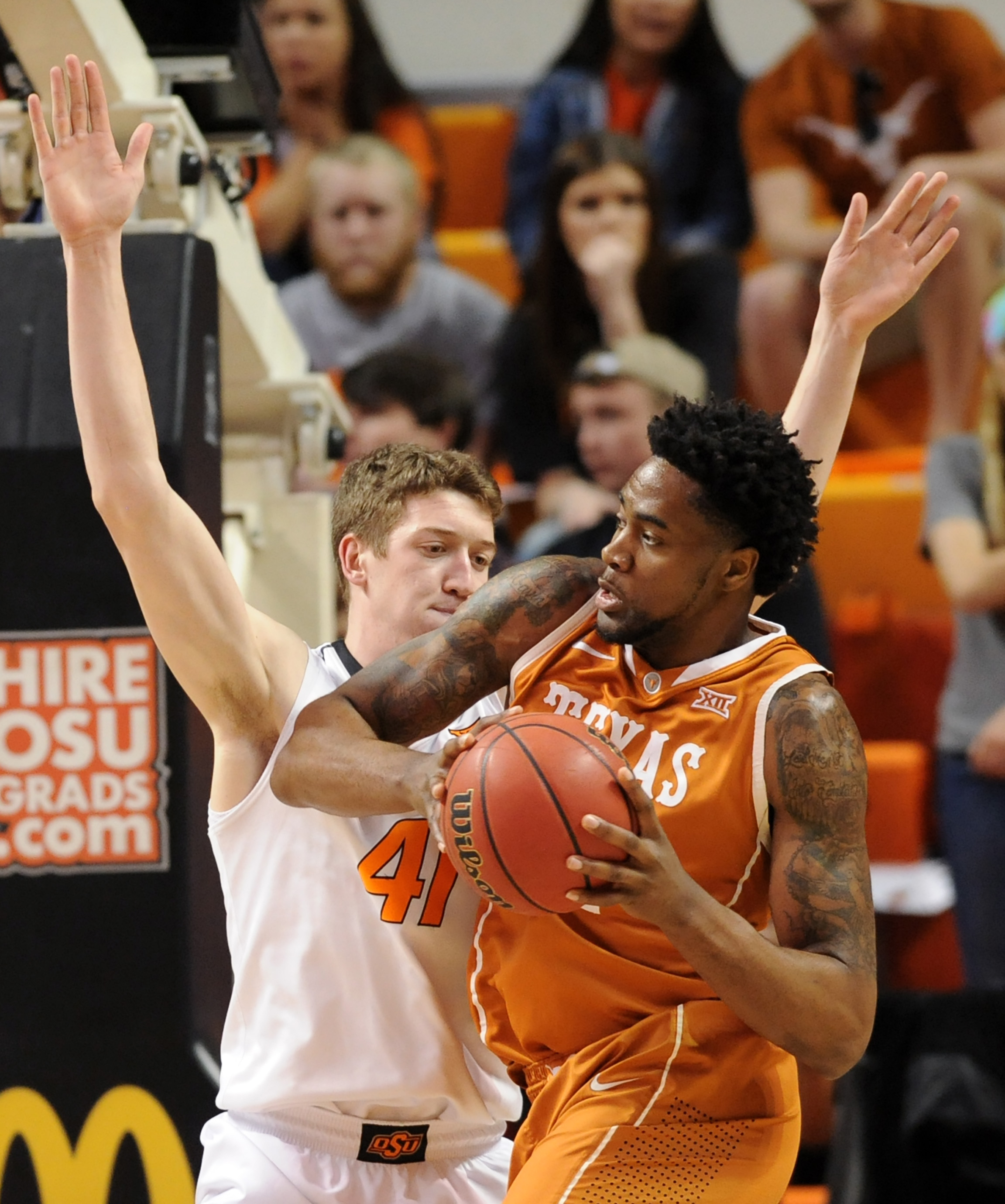 Texas center Prince Ibeh, right, looks for a path around Oklahoma State forward Mitchell Solomon, in the first half of an NCAA college basketball game in Stillwater, Okla., Friday, March. 4, 2016. (AP Photo/Brody Schmidt)