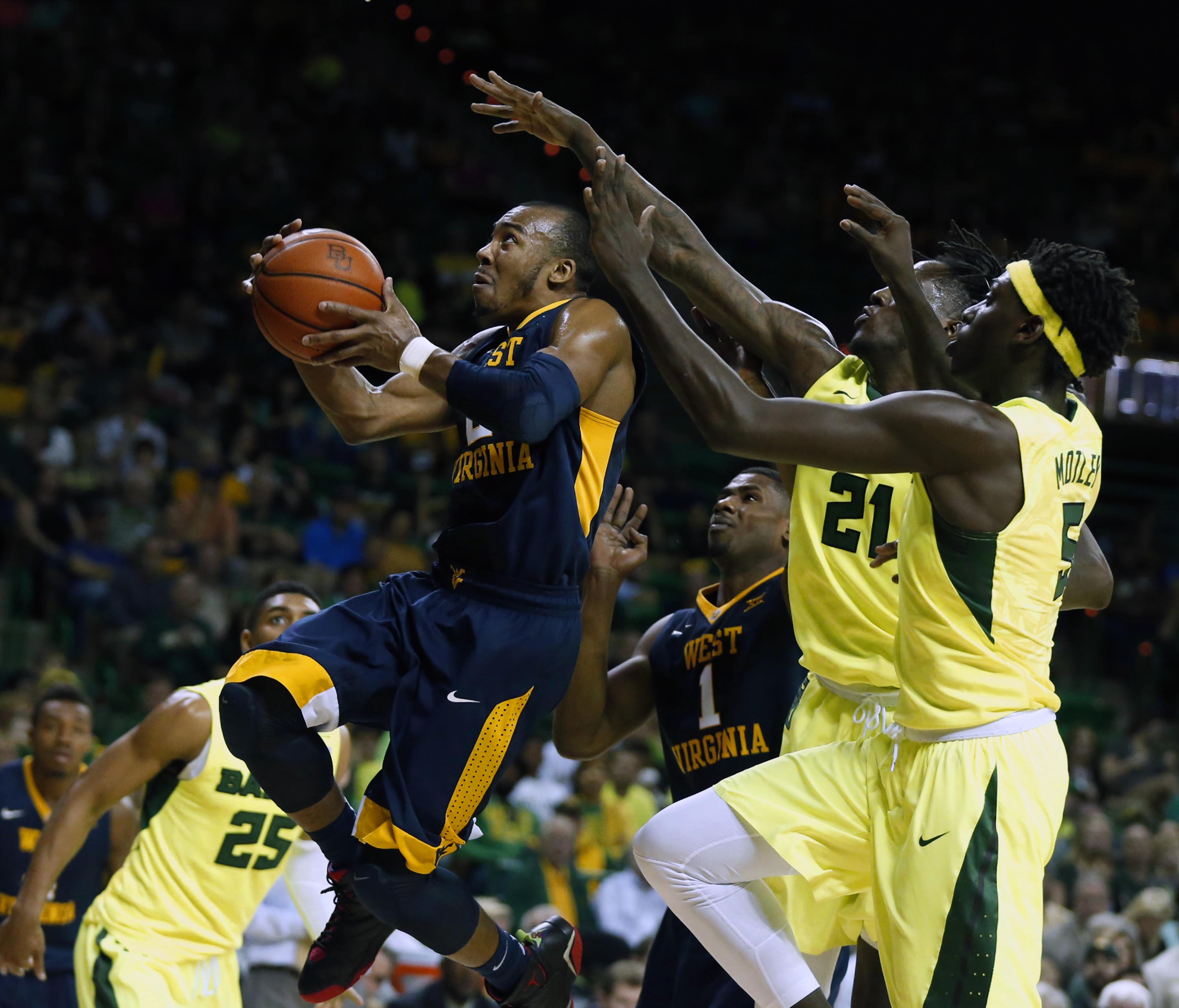 West Virginia guard Jevon Carter drives past Baylor forward Taurean Prince and forward Johnathan Motley, right,  in the first half of an NCAA college basketball game, Saturday, March 5, 2016, in Waco, Texas. (AP Photo/Rod Aydelotte)