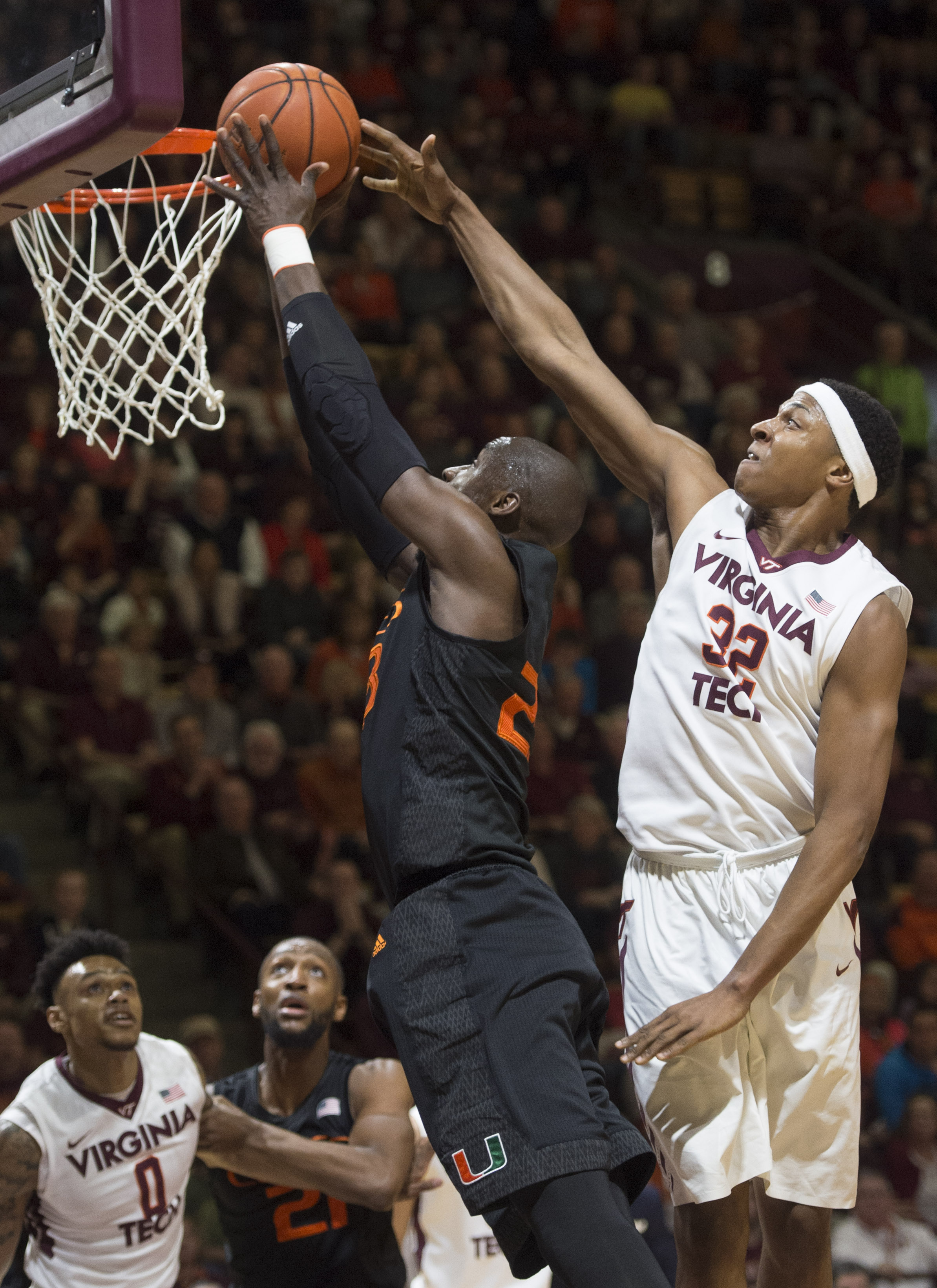 Miami's Tonye Jekiri, left, goes up for a basket against  Virginia Tech's  Zach LeDay during the first half of an NCAA college basketball game Saturday, March 5, 2016, in Blacksburg, Va. (AP Photo/Don Petersen)