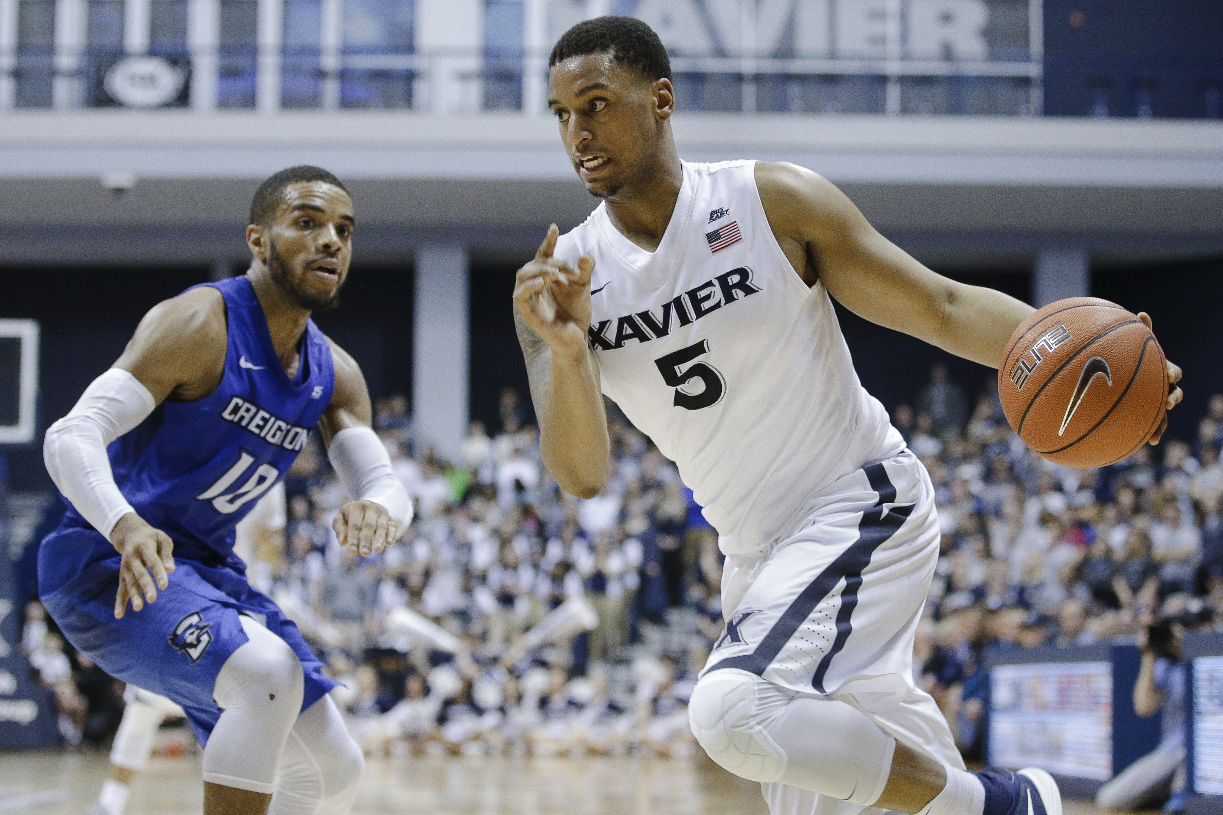 Xavier's Trevon Bluiett (5) drives past Creighton's Maurice Watson Jr. (10) during the second half of an NCAA college basketball game, Saturday, March 5, 2016, in Cincinnati. Xavier won 98-93. (AP Photo/John Minchillo)